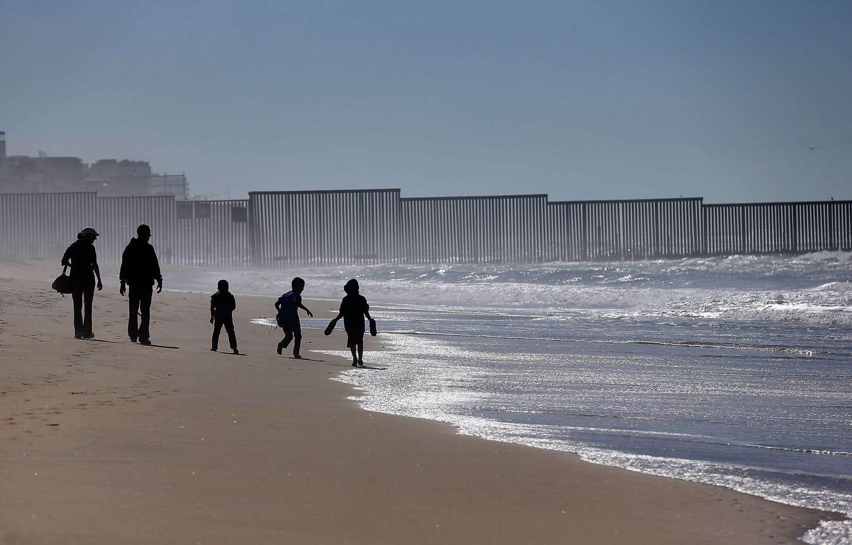 Une famille marche sur la plage à San Diego, du côté américain du mur frontalier qui sépare les États-Unis du Mexique et s'étire jusque dans la mer.