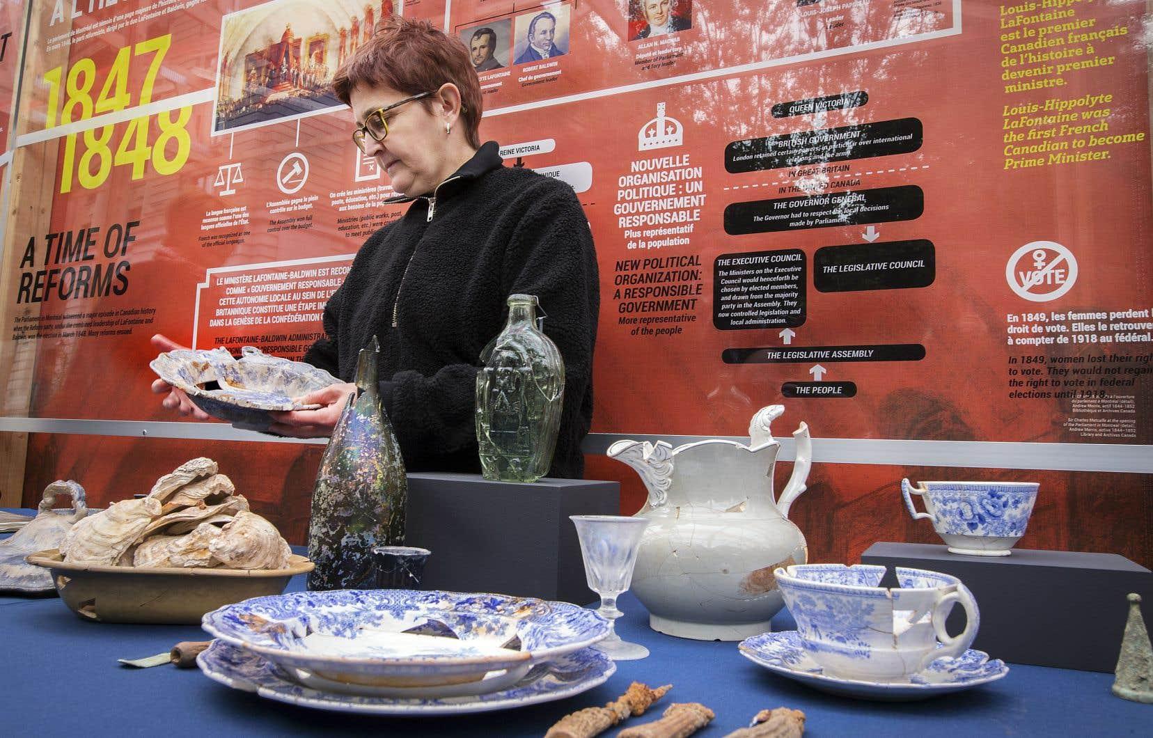 Louise Pothier, archéologue en chef au musée Pointe-à-Callière, observe quelques-uns des artefacts: assiettes, bols et coutellerie sans doute utilisés au restaurant du parlement, qui ont été récupérés, tout comme des coquilles d'huîtres.