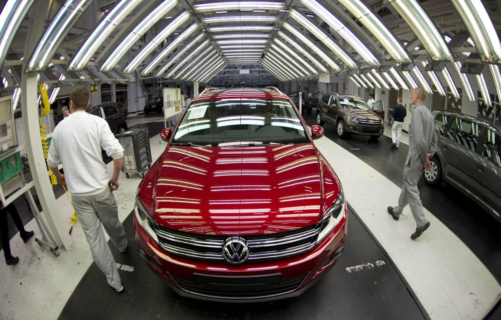 Des employés de Volkswageninspectent une voiture sortant d'une ligne d'assemblage en Allemagne.