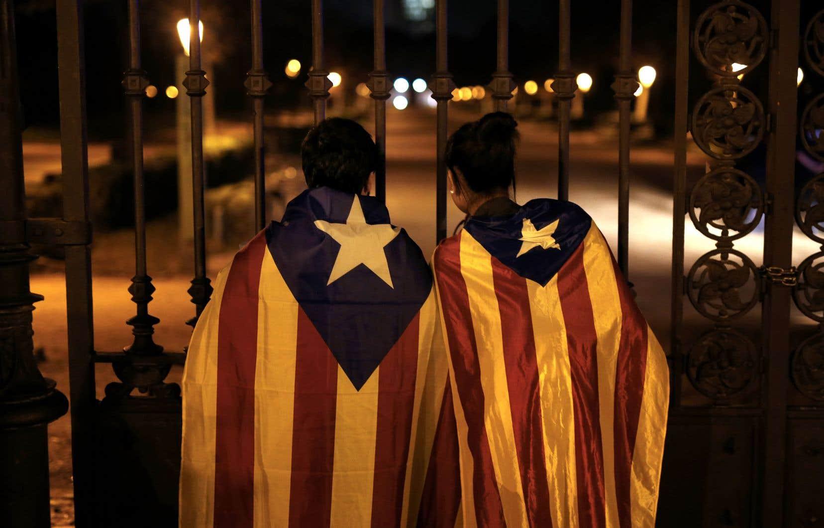 Deux manifestants indépendantistes regardent à travers les grilles du parlement catalan, à Barcelone.