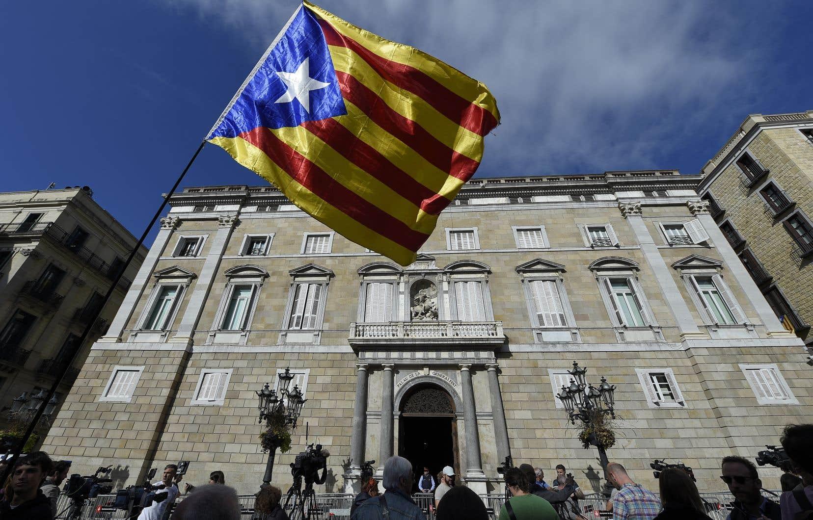 Un homme fait flotter le drapeau aux couleurs de l'indépendance catalane devant le palais de la Généralité, siège de l'exécutif, lundi matin.