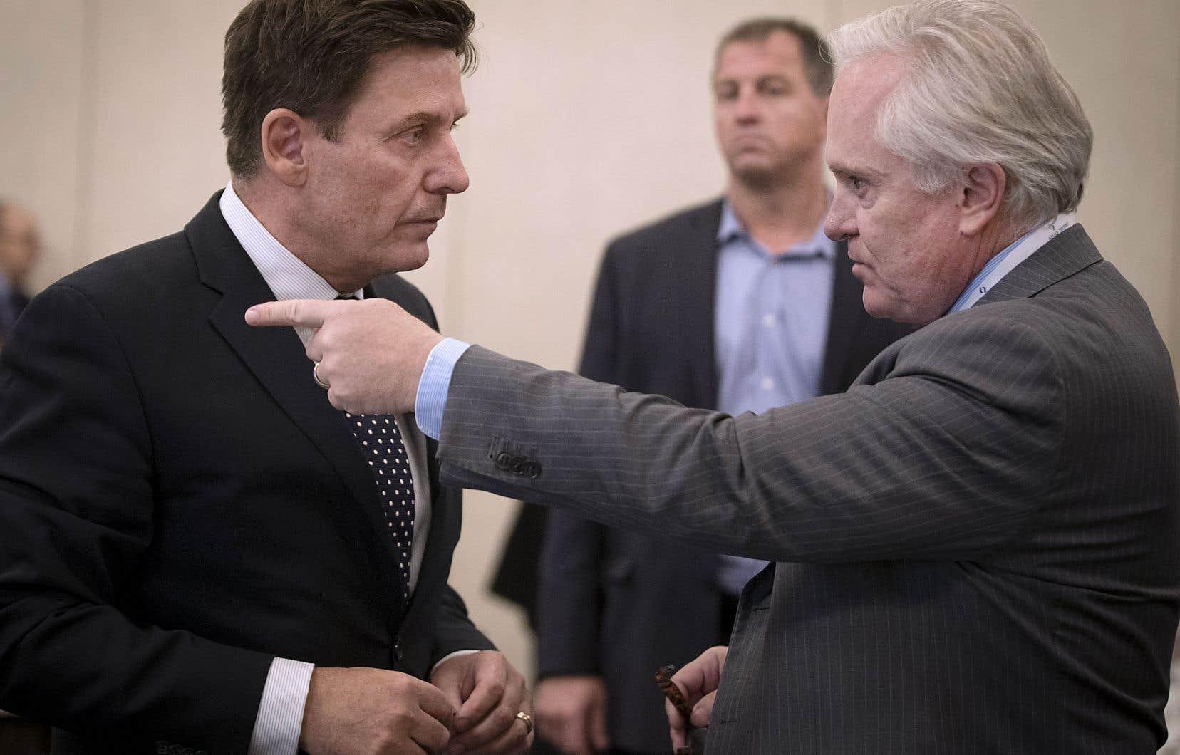 Le ministre de l'Énergie et des Ressources naturelles, Pierre Moreau, discute avec le président de l'Association pétrolière et gazière du Québec, Michael Binnion, également président de l'entreprise Questerre.