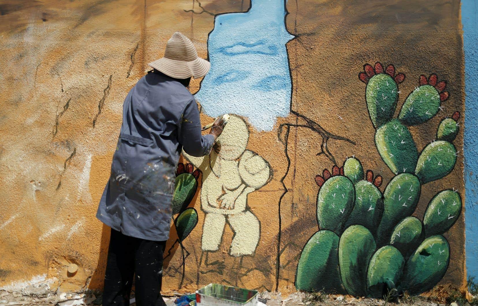Un artiste palestinien réalise une murale sur le mur de l'école Beit Hanoun, gérée par les Nations unies, dans le nord de la bande de Gaza.