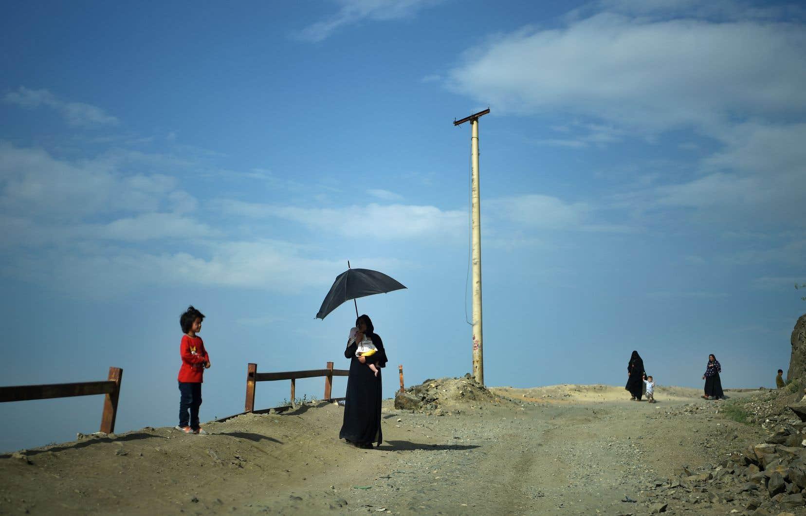 Des Afghanes, accompagnées de leurs enfants, se promènent sur la route de la colline de Kaboul.