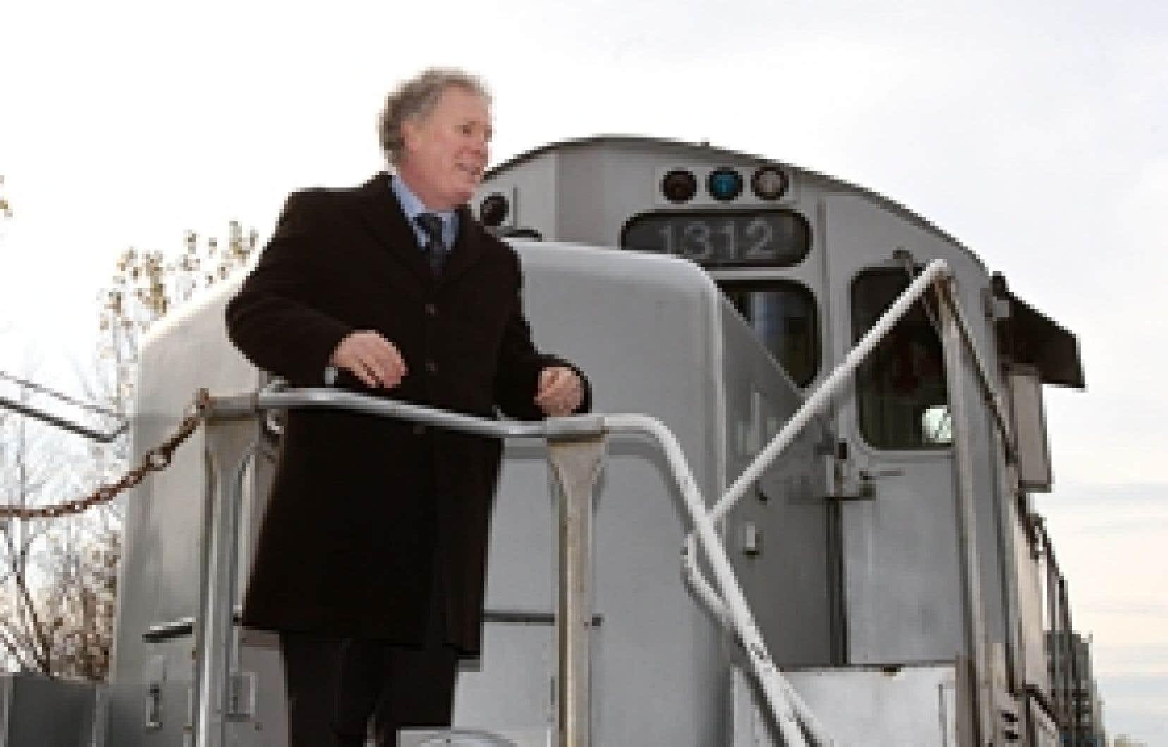 Le chef libéral, Jean Charest, installé sur une locomotive, a annoncé qu'il augmenterait le service des trains de banlieue.