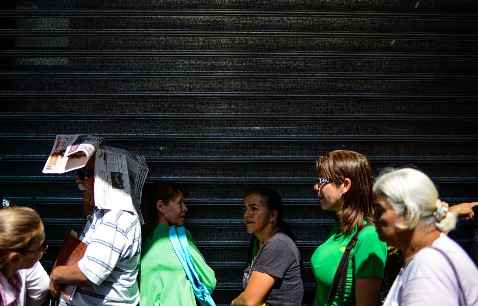 Les gens font la queue devant un supermarché à Caracas pour acheter des denrées alimentaires et des produits ménagers de base, le 10 novembre.