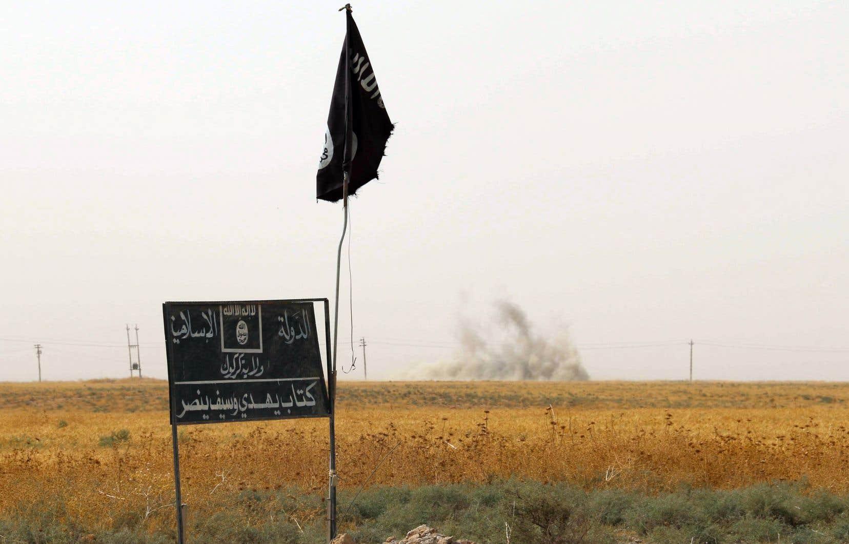 De la fumée se dresse derrière un drapeau et une bannière du groupe État islamique, dans le district de Daquq, en 2015.