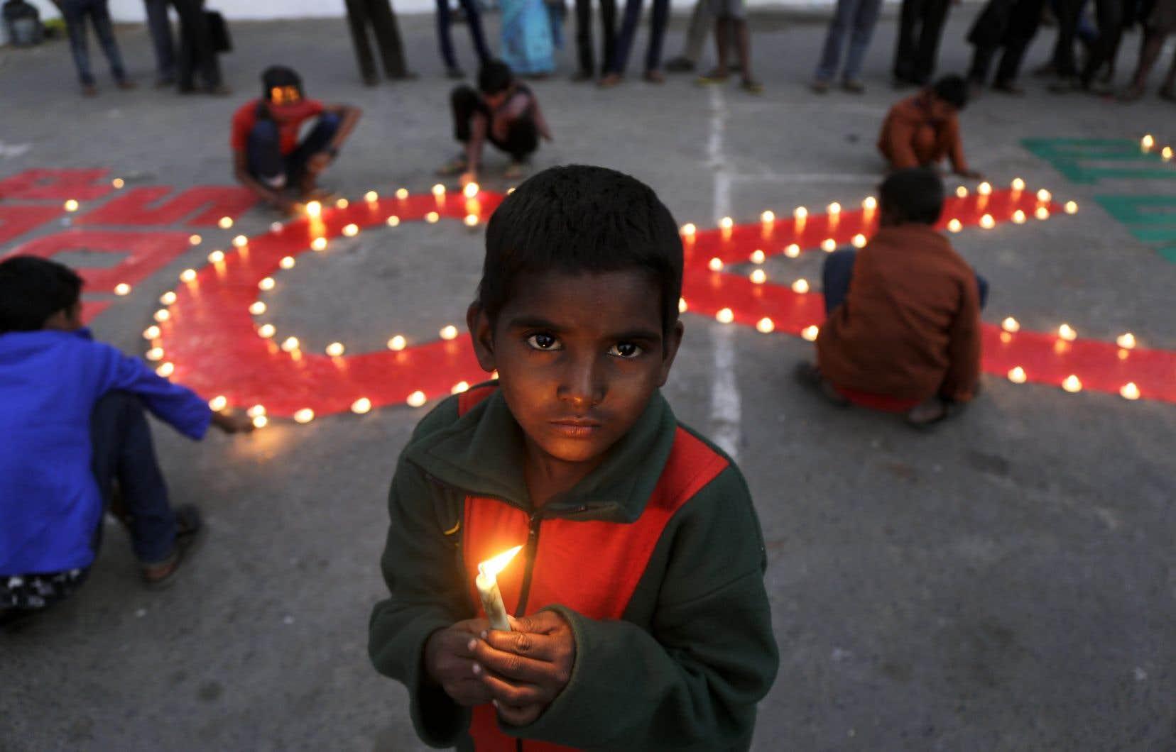 À l'occasion de la Journée mondiale du sida, un petit garçon indien tient une chandelle allumée en signe de soutien aux victimes du sida.