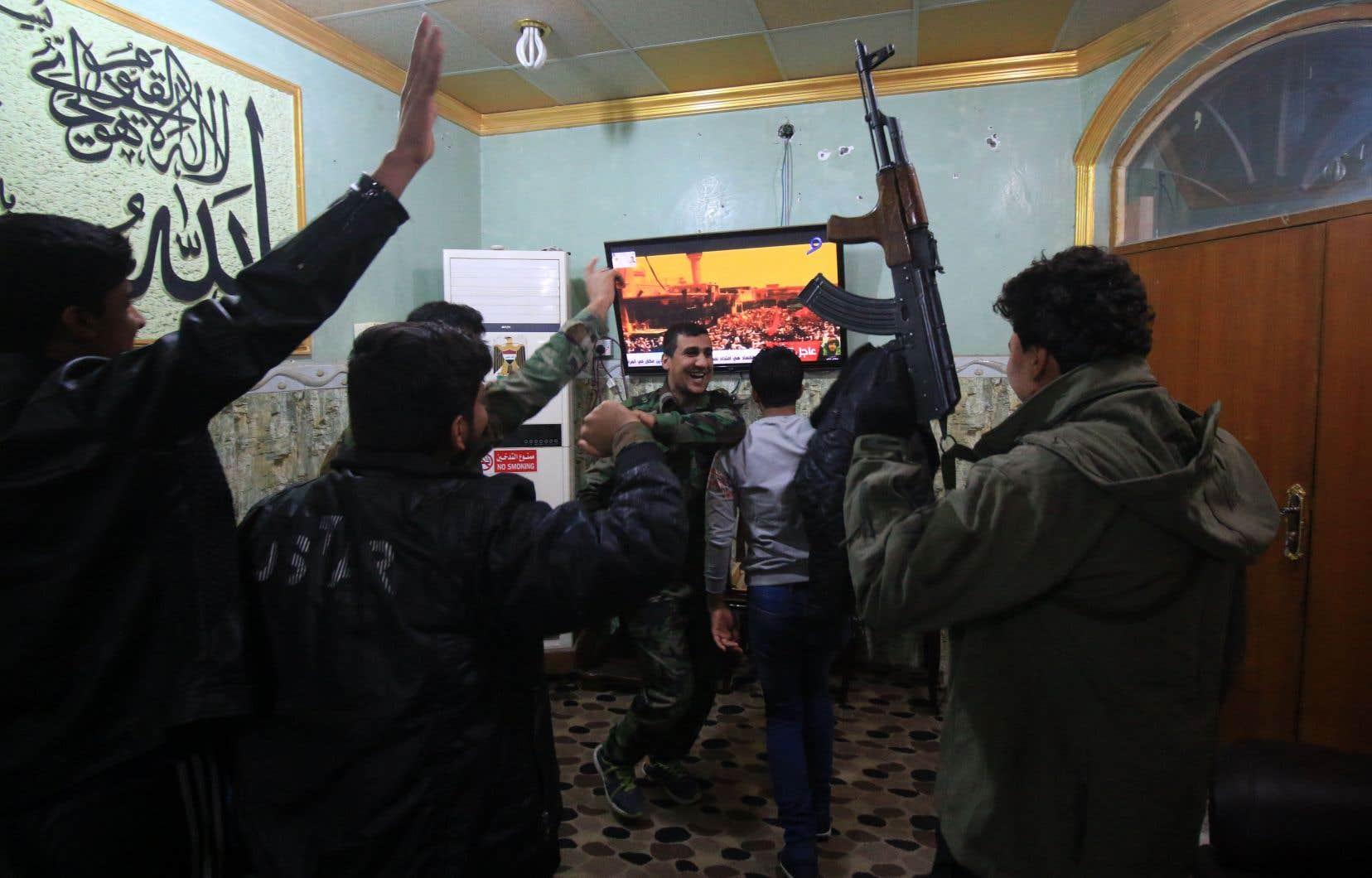 Des paramilitaires irakiens se réjouissent de l'annonce télévisée du premier ministreHaider al-Abadi, samedi.