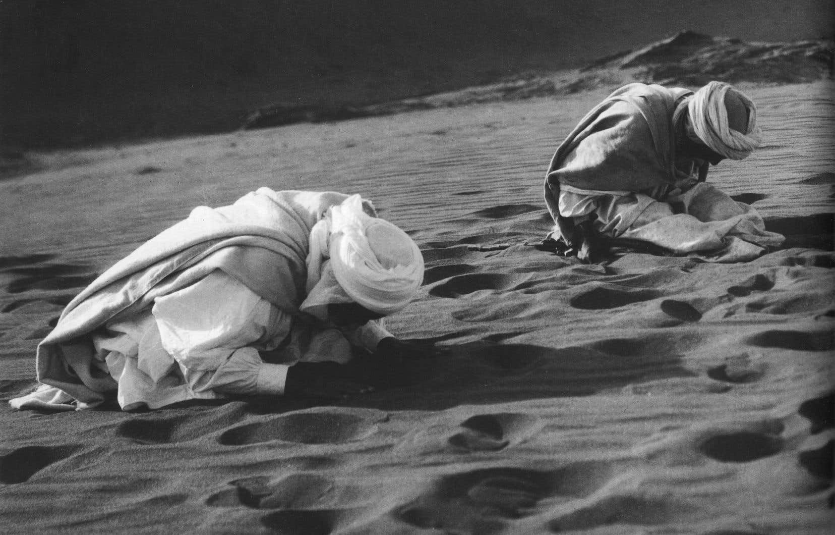 Tournés vers la Kaâba, deux hommes prient dans le désert du Sahara, en Algérie. Une image universelle, estime le romancier Tahar Ben Jelloun.