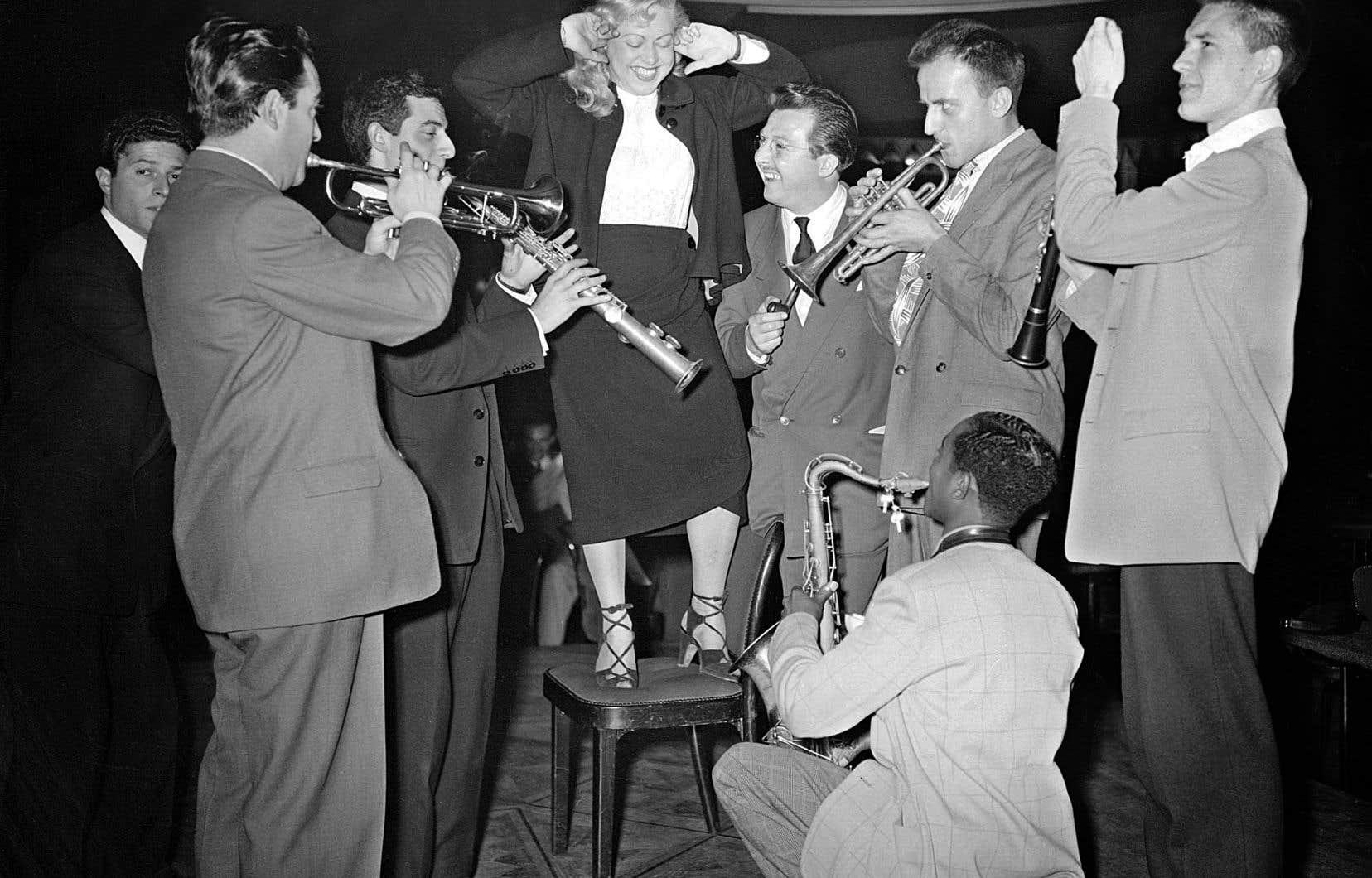 Les musiciens Don Byas (à genoux), Claude Luter, Boris Vian, Aimé Barelli et Jacques Diéval (de droite à gauche), autour de Michelle Vian, répètent au Lido de Paris le 4mai 1948 avant l'ouverture du Festival international de jazz.