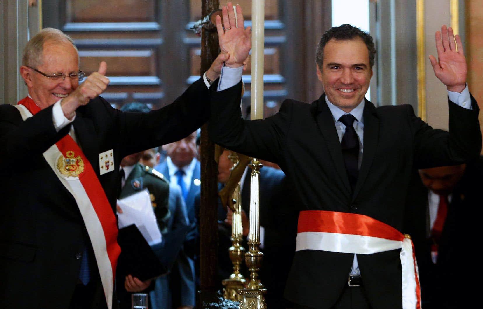 Le président péruvien, Pedro Pablo Kuczynski (à gauche), lève la main de son ministre de la Culture, Salvador del Solar, lors de sa cérémonie d'investiture au palais présidentiel de Lima le 5 décembre 2016.