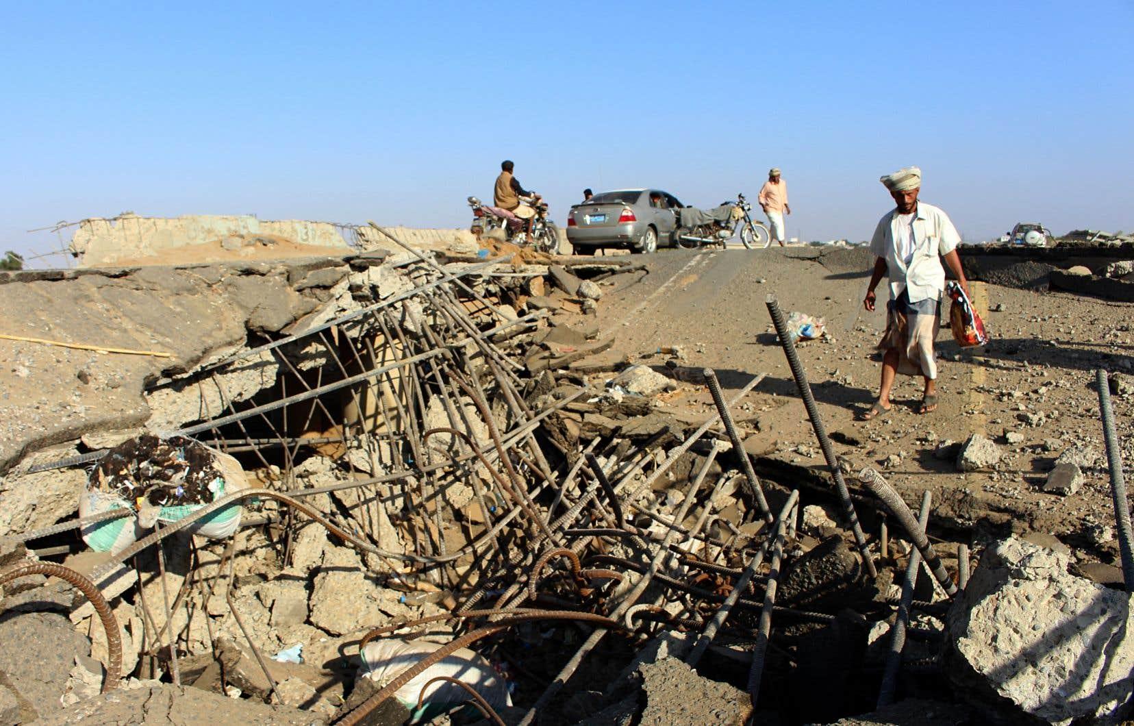 Des hommes yéménites inspectent les dégâts causés par une frappe aérienne dirigée par l'Arabie saoudite sur un pont entre les régions d'Abbas et de Harad, le 25 décembre.