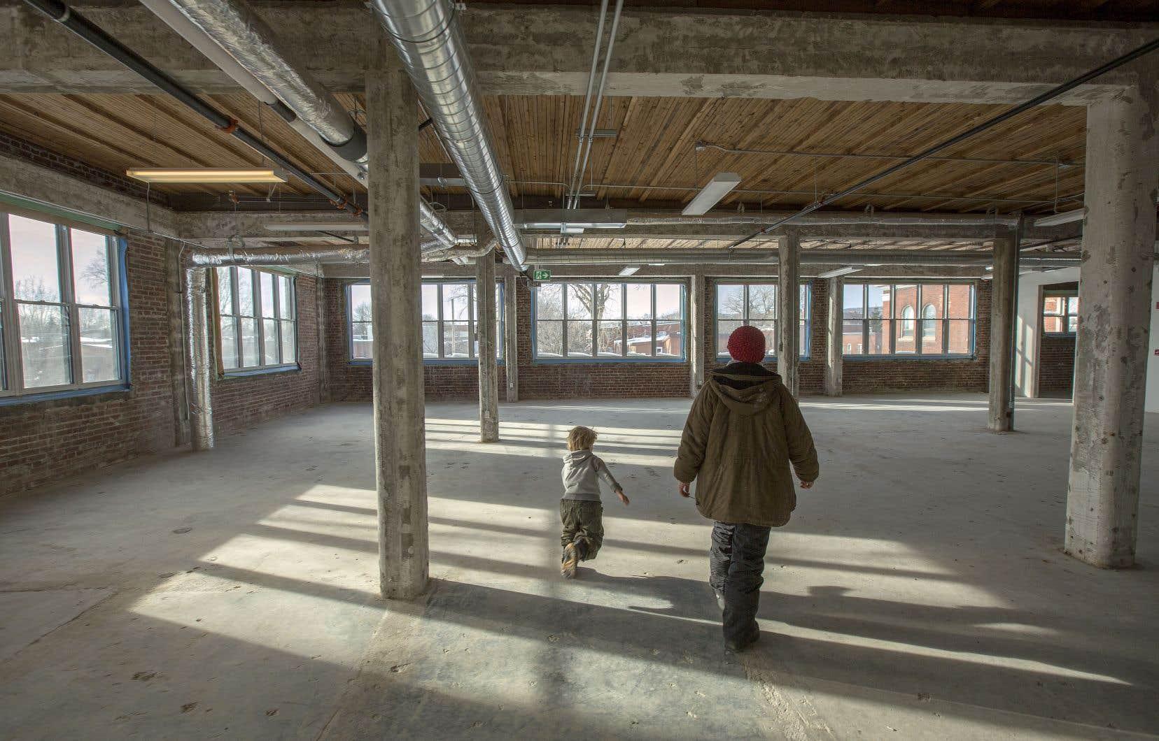 Judith Cayer, chargée de projet et de développement au Collectif 7 à nous, marche à travers les grands espaces du rez-de-chaussée avec son fils. La première phase du projet Bâtiment 7 permet de rénover ce grand édifice industriel largement vitré pour accueillir 13 projets des plus diversifiés.