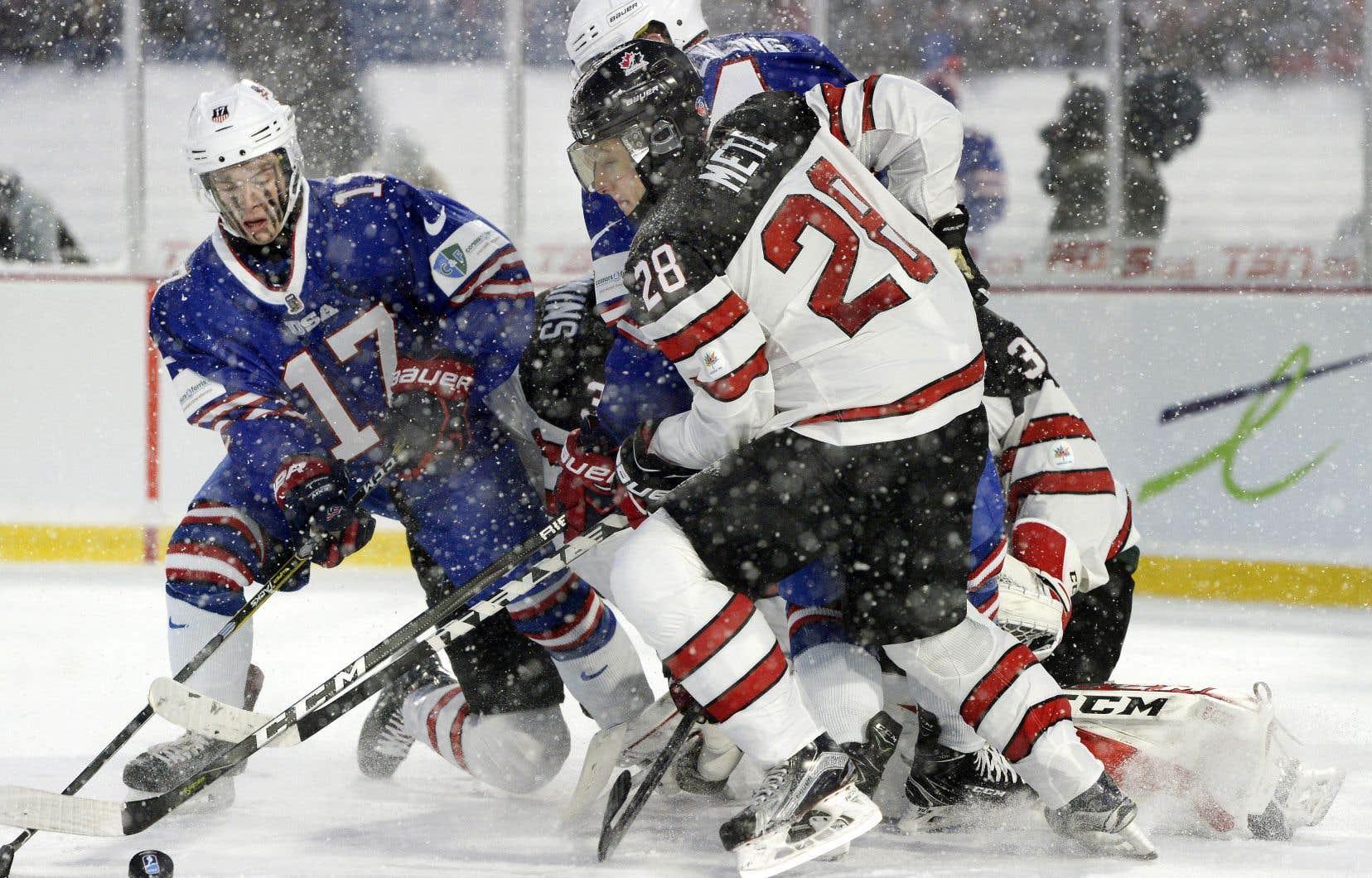 Sous la neige qui tombait sur ce match en plein air — le premier de l'histoire du Championnat —, les joueurs états-unien Kailer Yamamoto (17) et canadien Victor Mete (28) bagarraient dur lors de la seconde période.