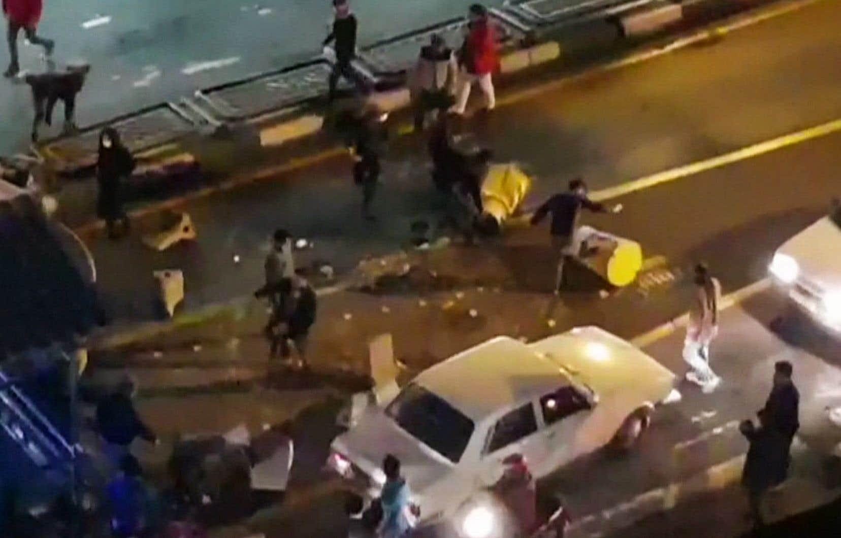 Une capture d'écran d'une vidéo distribuée par l'agence iranienne Mehr News montre un groupe d'hommes poussant des barrières dans une rue de Téhéran le 30 décembre 2017.