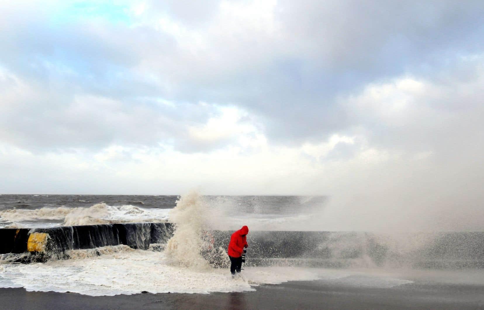 Un photographe vérifie son équipement après qu'une vague a cassé au-dessus du mur contenant habituellement les marées, à Brighton en Angleterre.