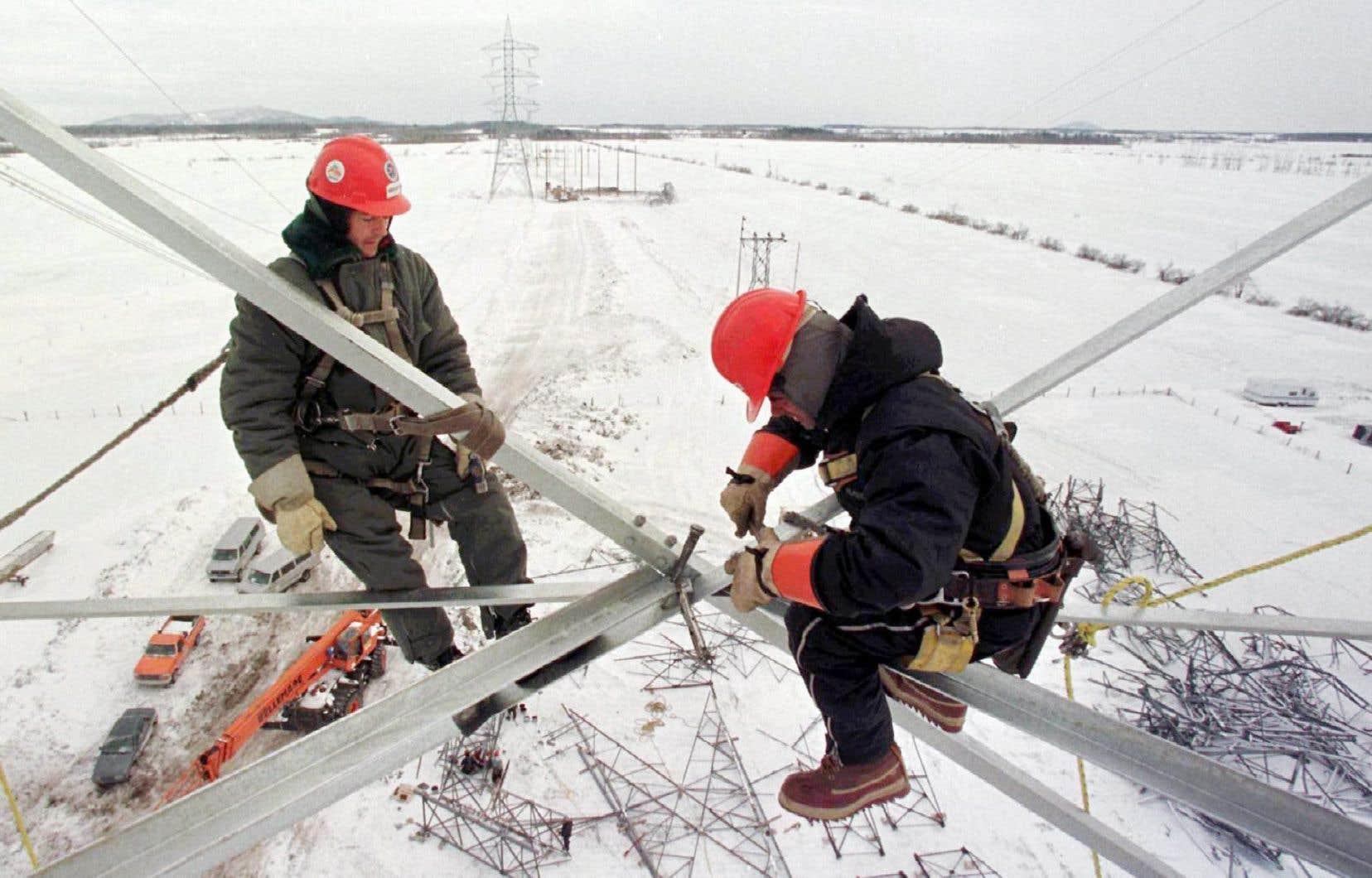 Les travailleurs Harold Boudreault, du Saguenay–Lac-Saint-Jean, et Roch Bresson, de Sacré-Cœur, assemblent un nouveau pylône au-dessus d'un champ d'Otterburn Park, en Montérégie.
