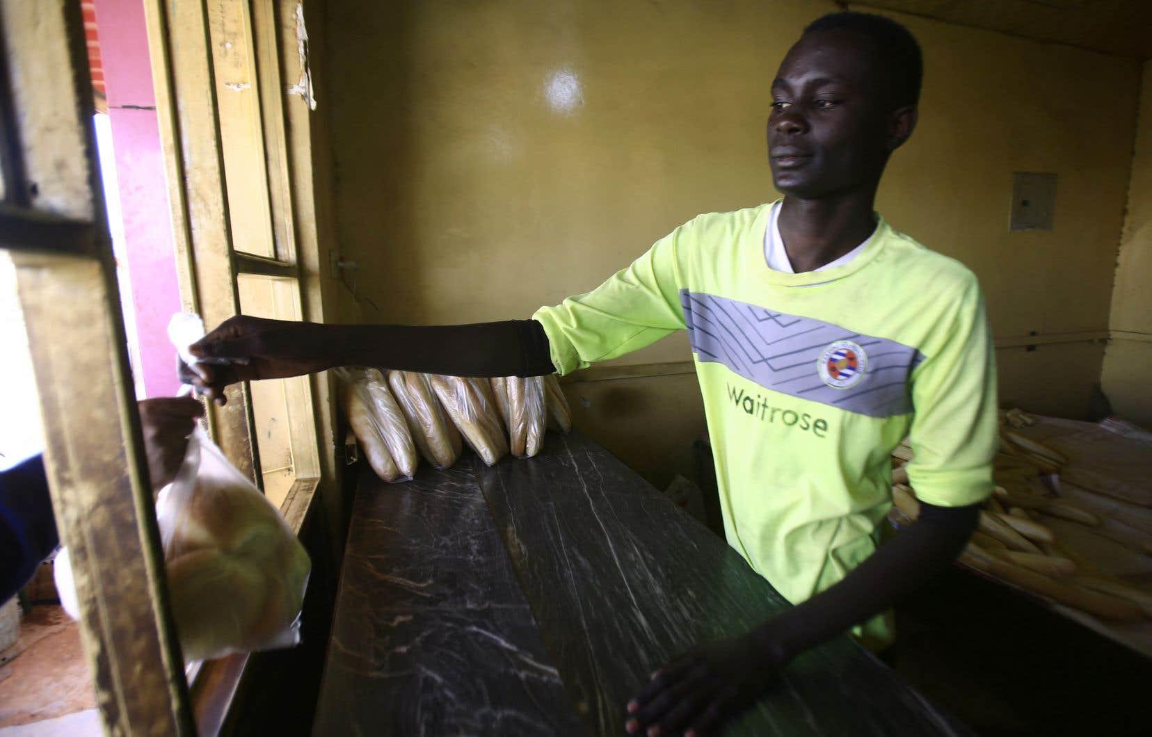 Un homme soudanais tend un sac de pain à un client dans une boulangerie de la capitale, Khartoum, le 5 janvier.