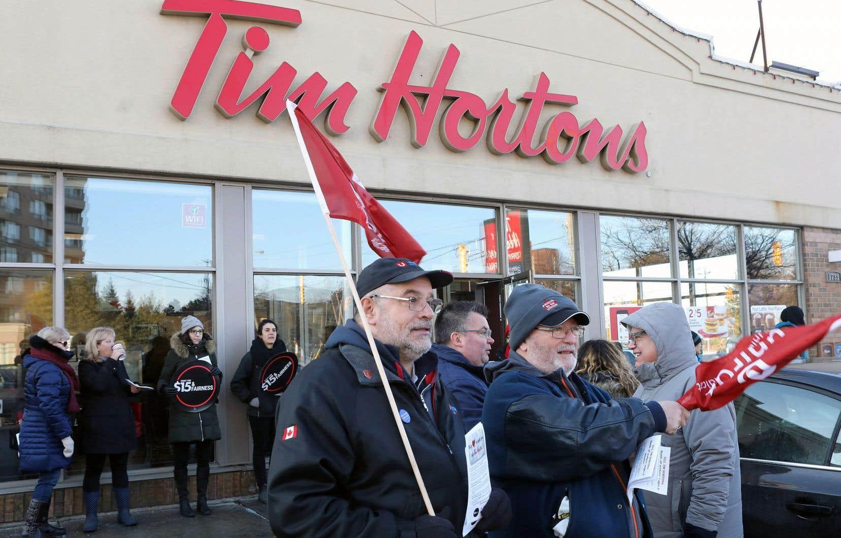 Des membres de l'Ontario Federation of Labour manifestaient devant un restaurant Tim Hortons, mercredi à Toronto.