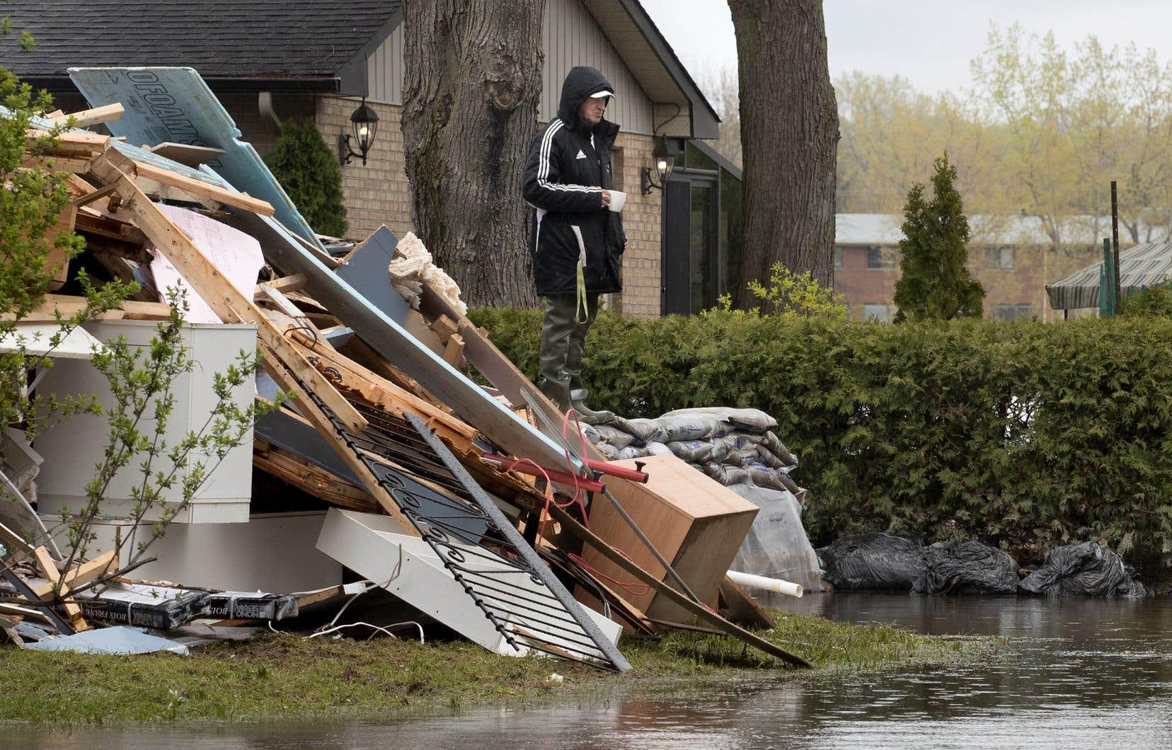 Un résidant de L'Île-Bizard profitant d'un moment de répit avant de poursuivre le nettoyage de sa maison, en mai 2017