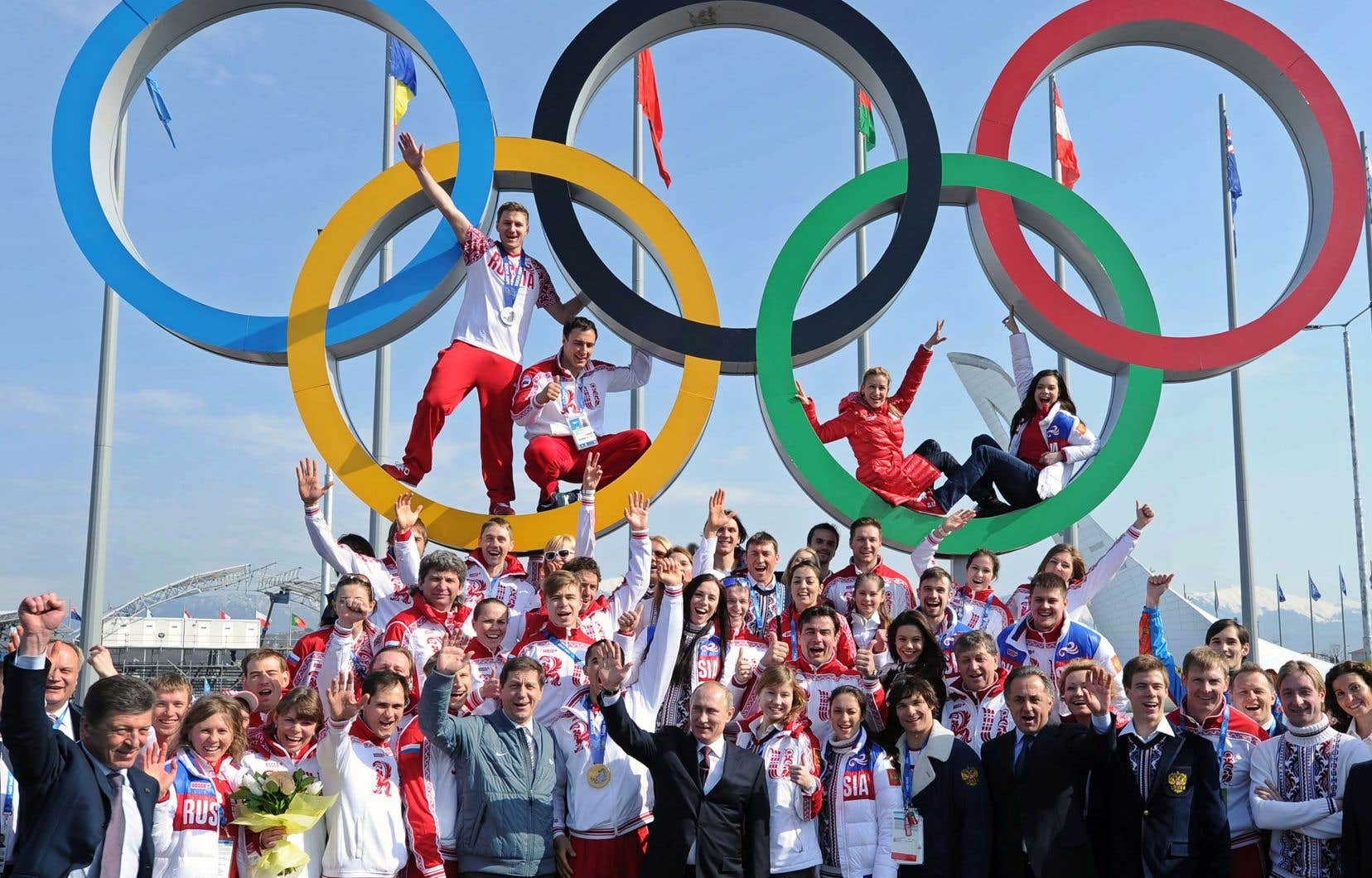 Le président de la Russie, Vladimir Poutine, pose avec des athlètes russes à Sotchi en 2014.