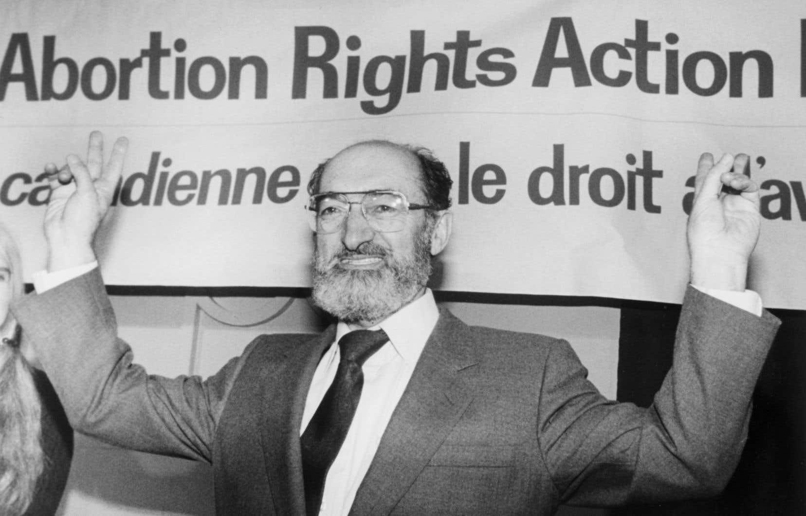 Le Dr Henry Morgentaler lève les bras en signe de victoire lors d'une conférence de presse à Toronto le 28 janvier 1988.