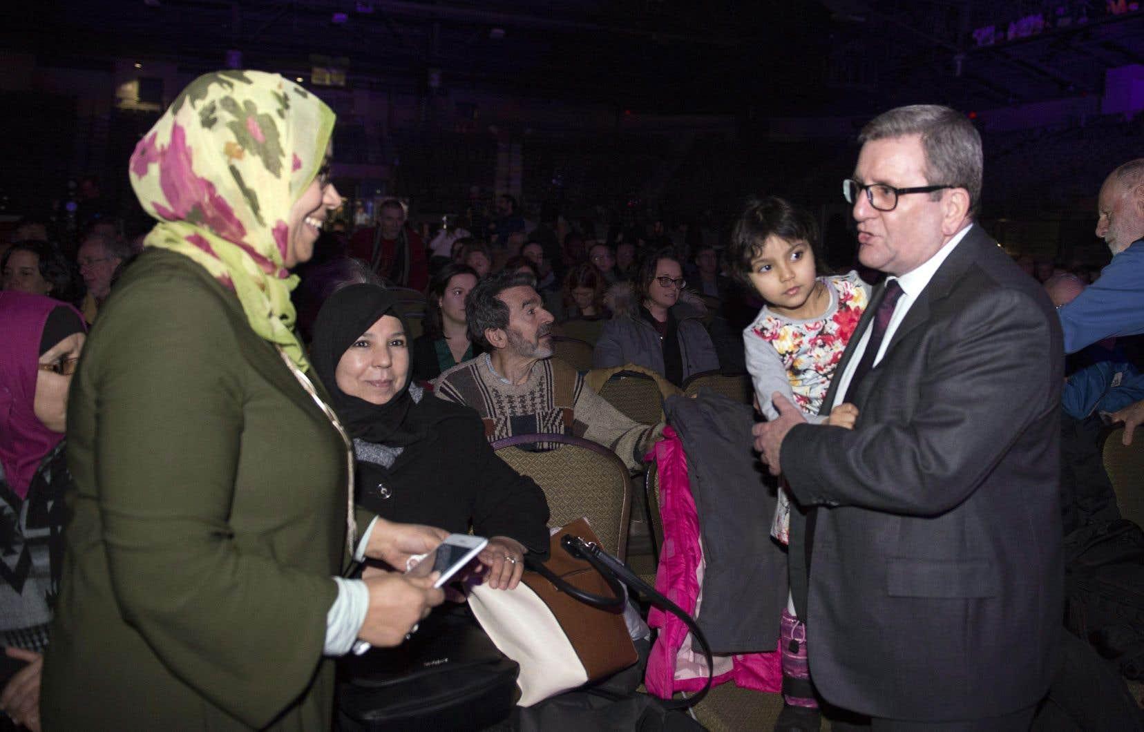 Le maire de Québec, Régis Labeaume, tient un enfant à un rassemblement organisé au Pavillon de la jeunesse pour souligner le premier anniversaire de l'attentat de la grande mosquée de Québec.