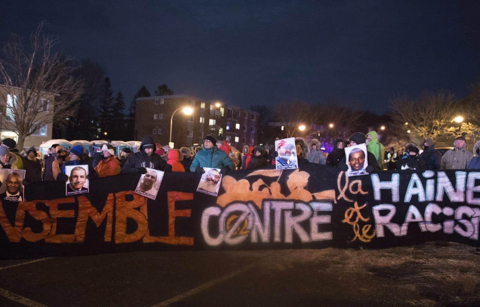 Des personnes rassemblées pour l'anniversaire de l'attentat de Québec portent une bannière contre le racisme lundi soir à Québec.