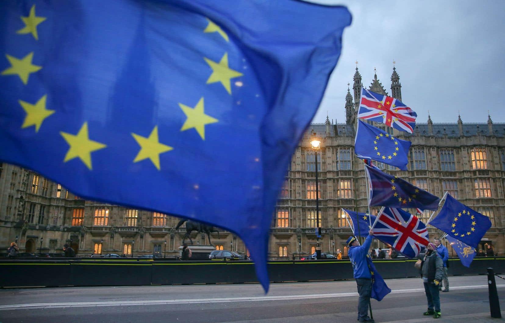 Des opposants au Brexit arboraient les drapeaux européen et britannique à l'extérieur du parlement, lundi à Londres.