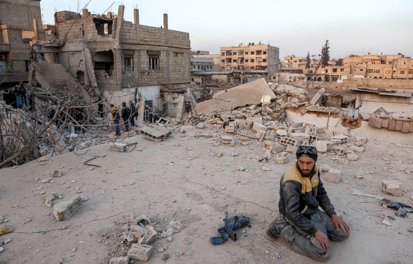 Un secouriste se tenait mardi à proximité d'un immeuble détruit par des bombardements du régime de Bachar al-Assad, dans la ville rebelle d'Arbin en Syrie.