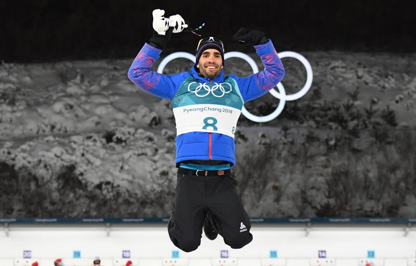 Le Français Martin Fourcade saute sur le podium lors de la cérémonie de victoire après avoir concouru dans le biathlon de 12,5 km masculin.
