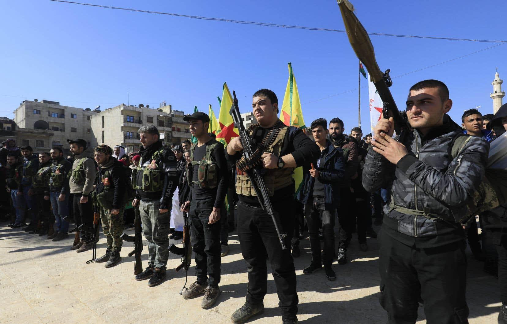 Des Kurdes syriens assistent à un défilé impromptu à Afrine, alors que les civils s'enrôlent pour combattre les troupes turques et les rebelles alliés contre les Unités de protection du peuple kurdes (YPG) dans la région frontalière de la Syrie, le 28 janvier 2018.