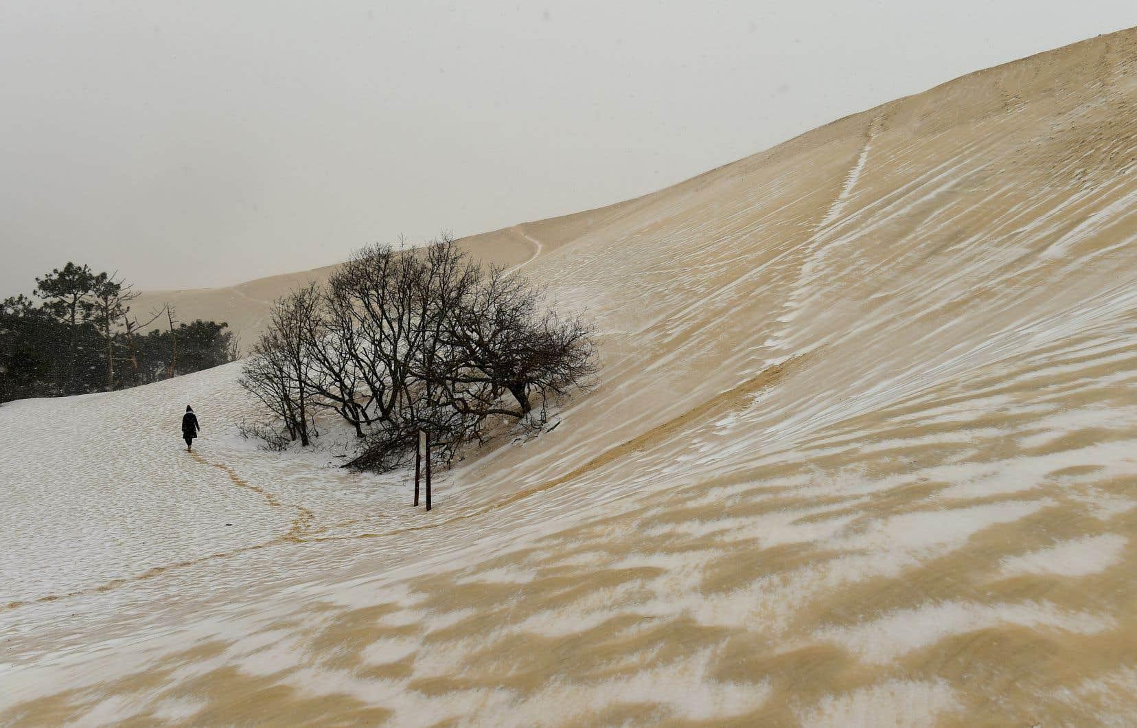 Une femme se promène sur la dune de sable partiellement couverte de neige du Pilat, à La Teste-de-Buch, dans le sud-ouest de la France.