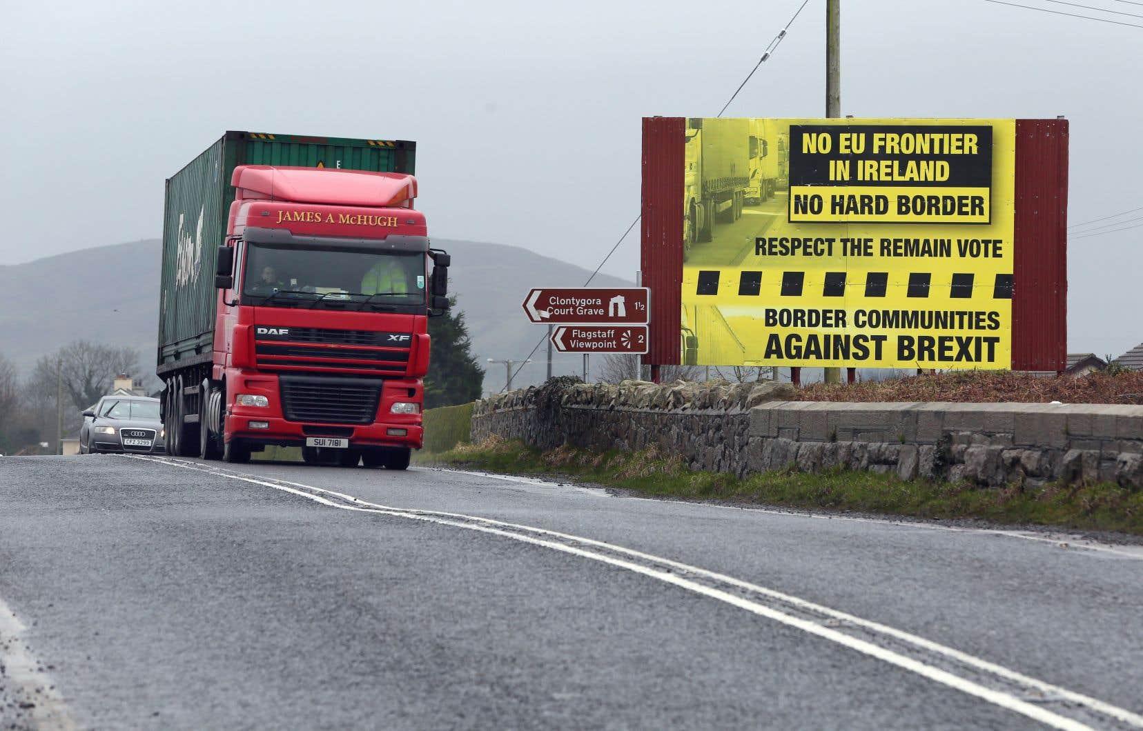 Des véhicules croisent une affiche présentant un message s'opposant à des contrôles frontaliers resserrés entre l'Irlande et l'Irlande du Nord.