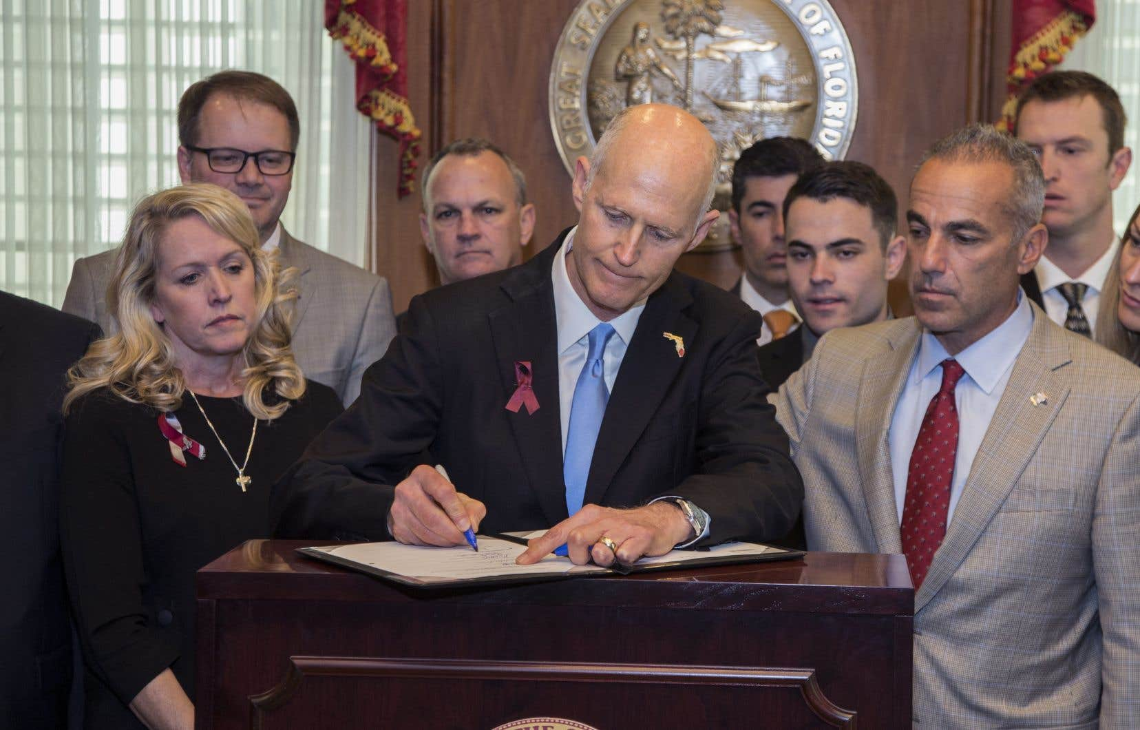 Le gouverneur de la Floride, Rick Scott, signe la Loi sur la sécurité publique de Marjory Stoneman Douglas dans le bureau du gouverneur au Florida State Capitol à Tallahassee, en Floride, le vendredi 9 mars 2018.