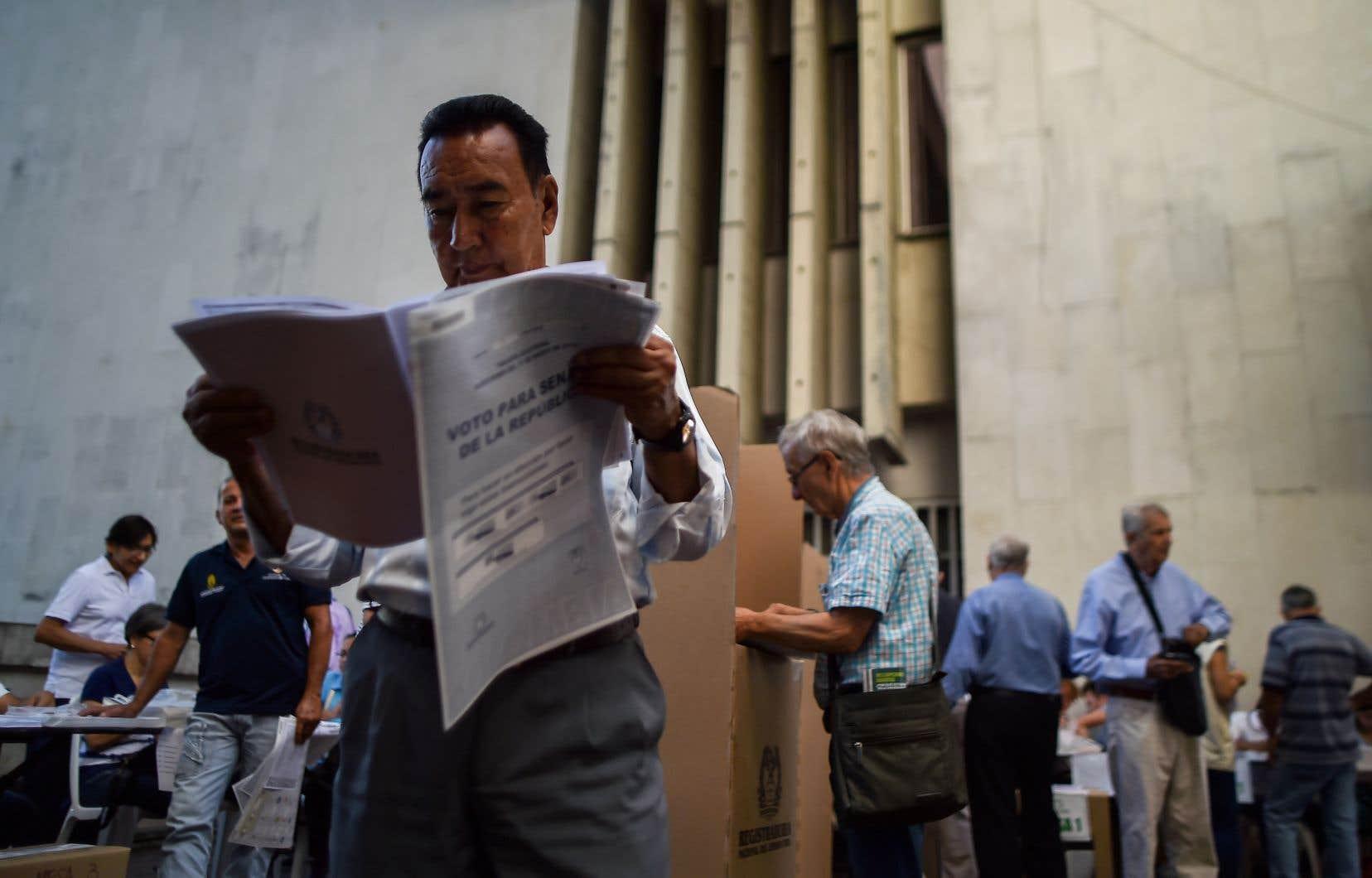 Un homme lit un bulletin électoral avant de voter dans un bureau de scrutin à Cali, département du Valle del Cauca, dimanche.