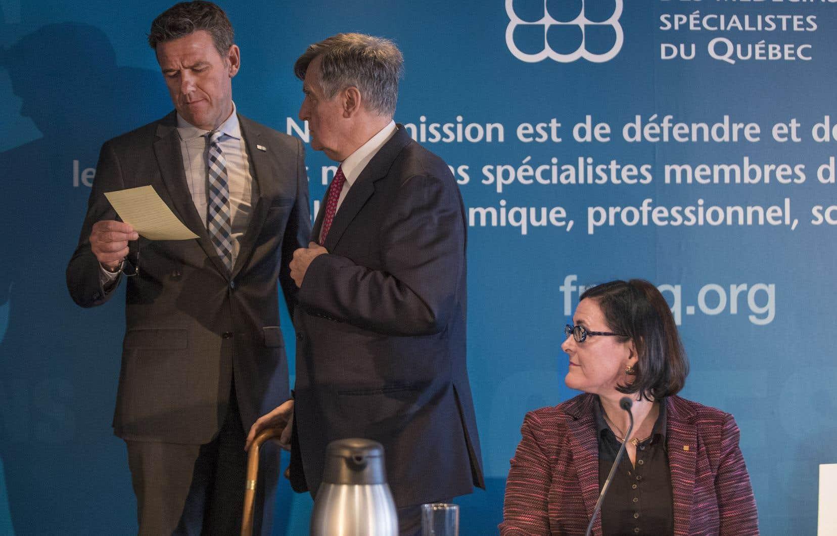 La présidente de la Fédération des médecins spécialistes, la DreDiane Francœur, regarde vers le directeur des affaires juridiques du syndicat, MeSylvain Bellavance, et l'ancien premier ministre Lucien Bouchard, qui agit comme conseiller spécial de la FMSQ.