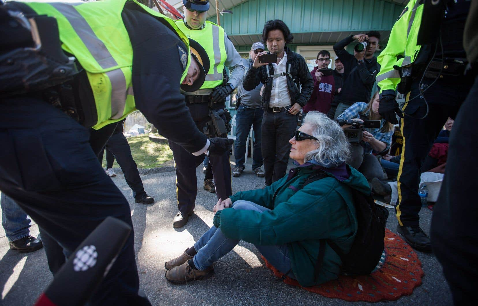 Des agents de la GRC arrêtent une manifestante assise à Burnaby, samedi.