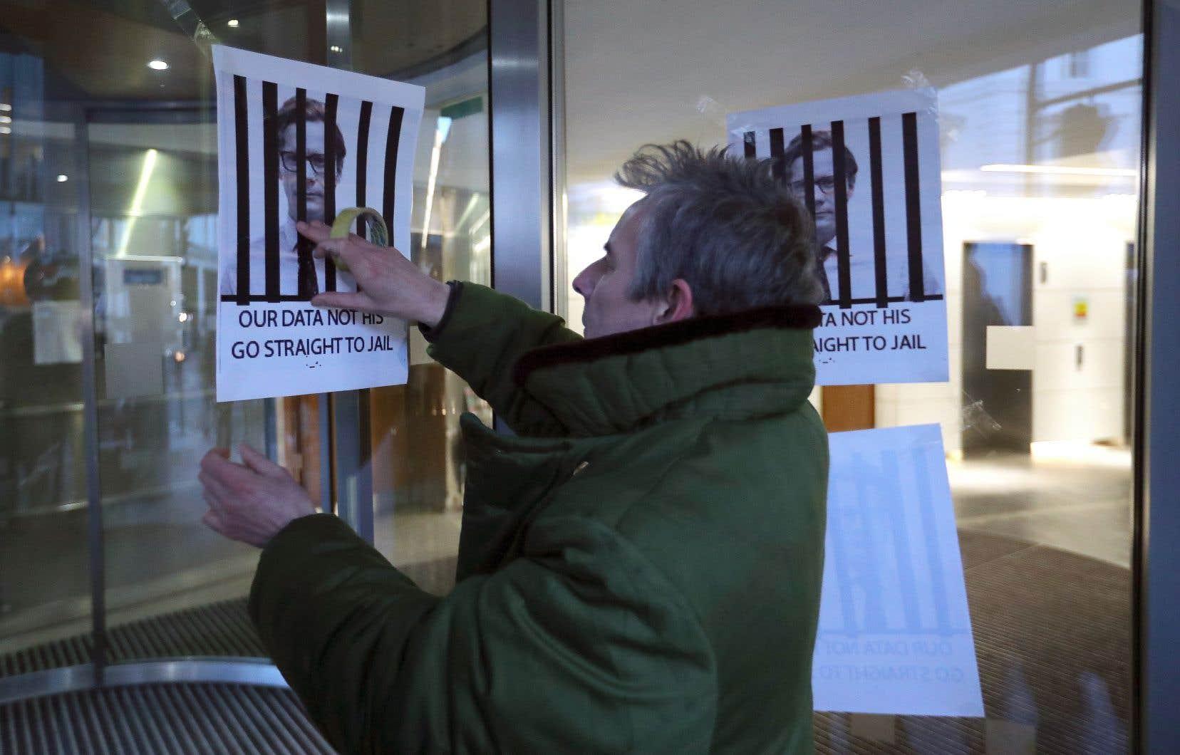 En Grande-Bretagne, un homme pose une affiche pour manifester sa colère contre Cambridge Analytica et son directeur général, Alexander Nix.