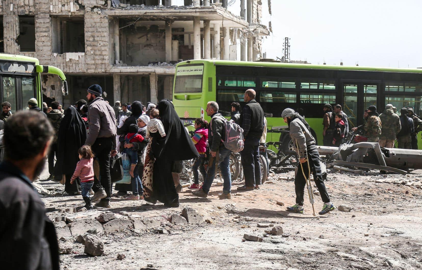 Un premier convoi de vingt-six bus a quitté dimanche l'enclave à destination d'Idleb, après un accord parrainé par la Russie.