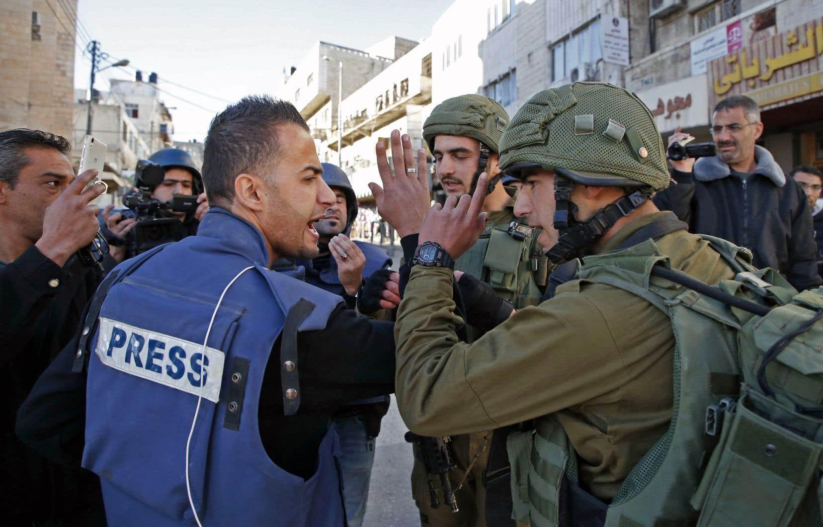 Un journaliste discutait avec un membre des forces armées israéliennes à Hébron, en décembre 2017, à la suite de la décision du président Trump de reconnaître Jérusalem comme capitale israélienne.