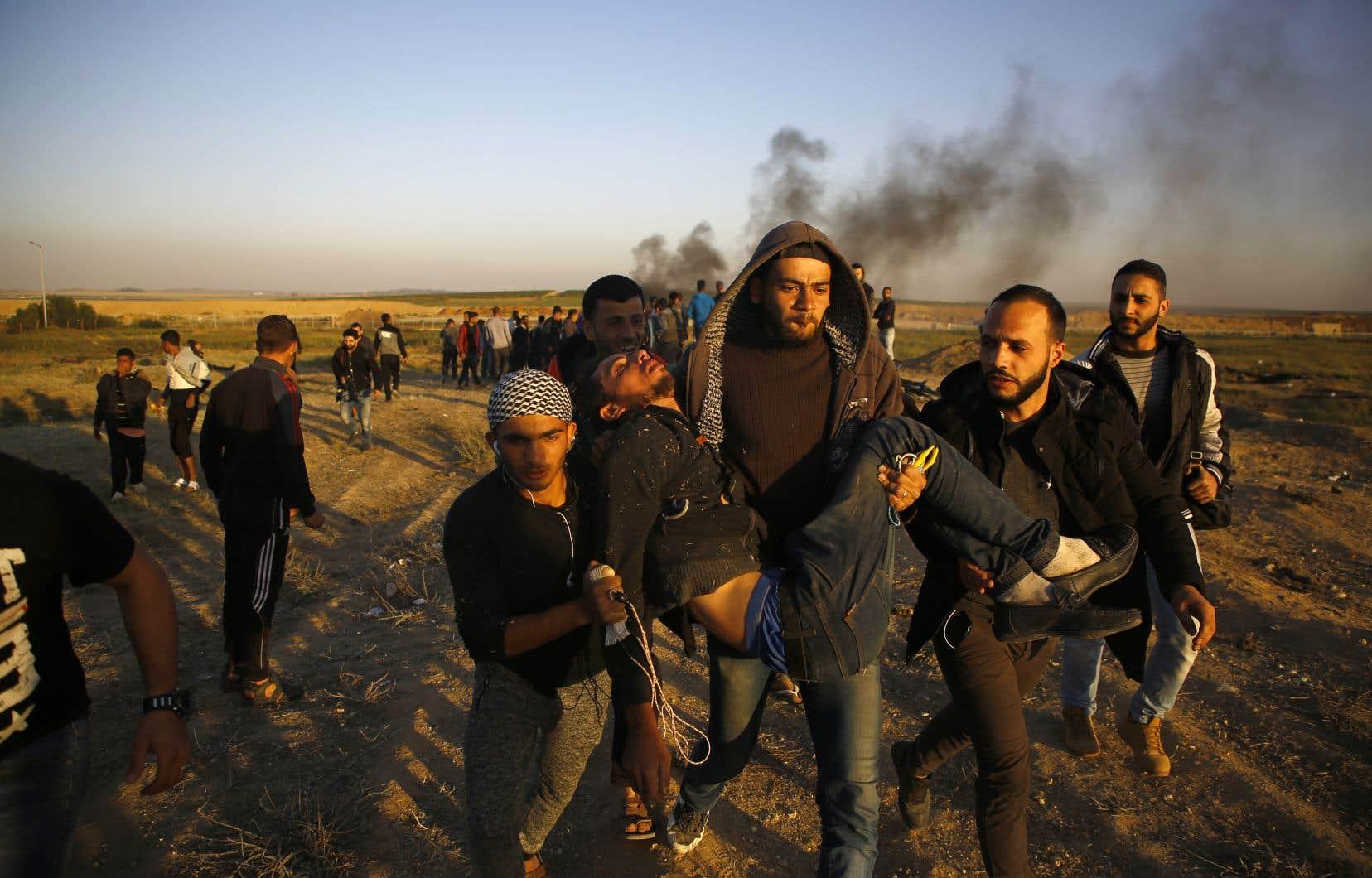 Des manifestants palestiniens portaient dans leurs bras un jeune homme blessé dimanche.