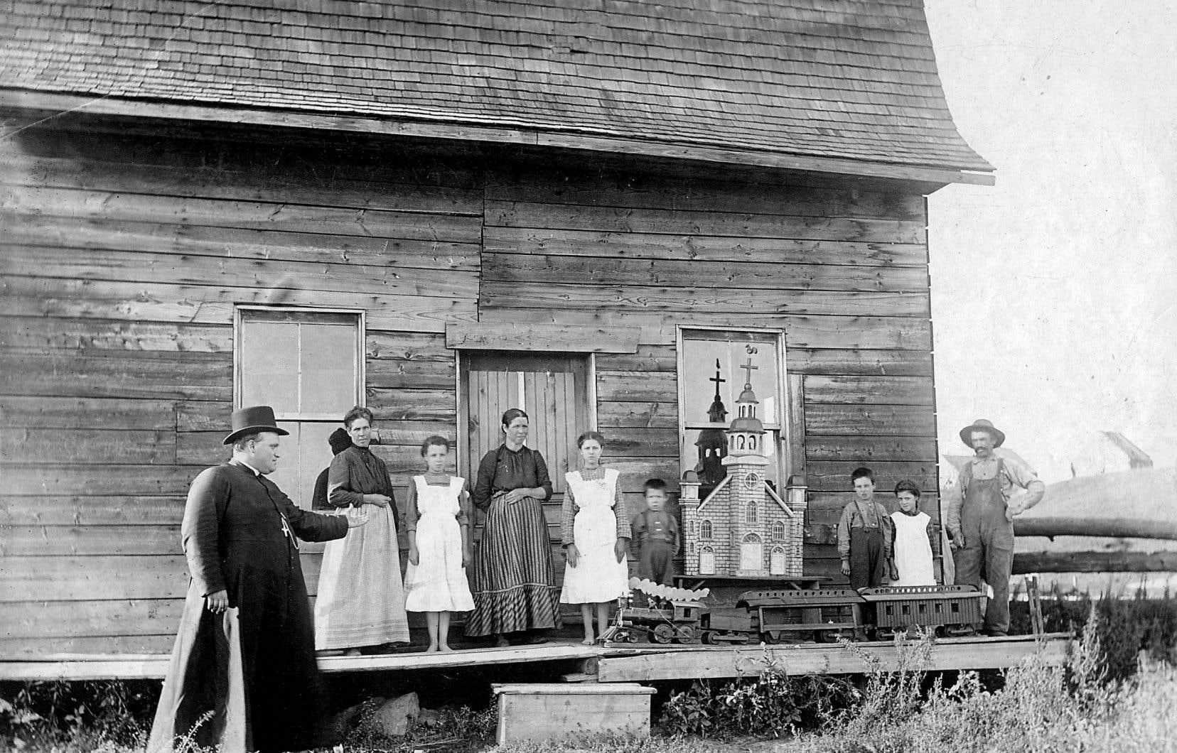 Le curé Labelle en visite chez des colons à Saint-Jovite avec une reproduction de l'église du village et du train du nord.