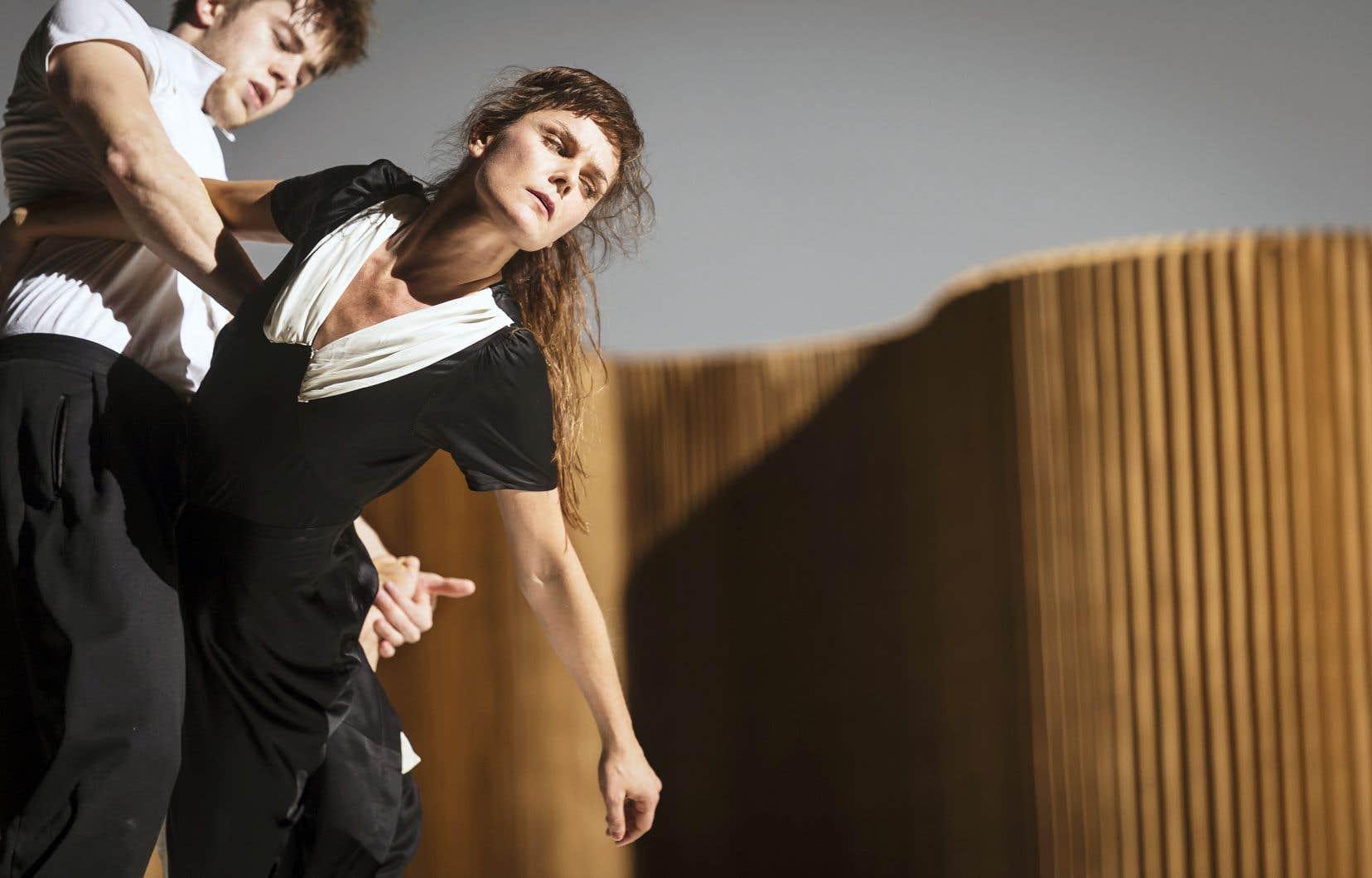 À l'avant-scène, un couple commence à se tirailler dans un pas de deux aux portées souples et fluides.