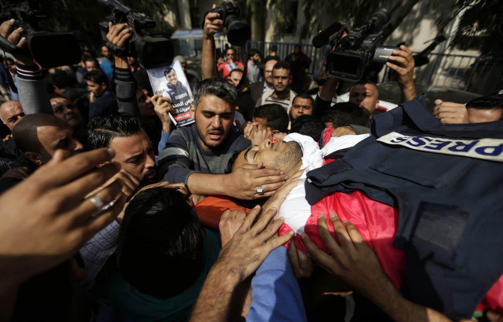 Des proches et des journalistes portent le corps du reporter palestinien Yasser Mourtaja, lors de ses funérailles à Gaza samedi.