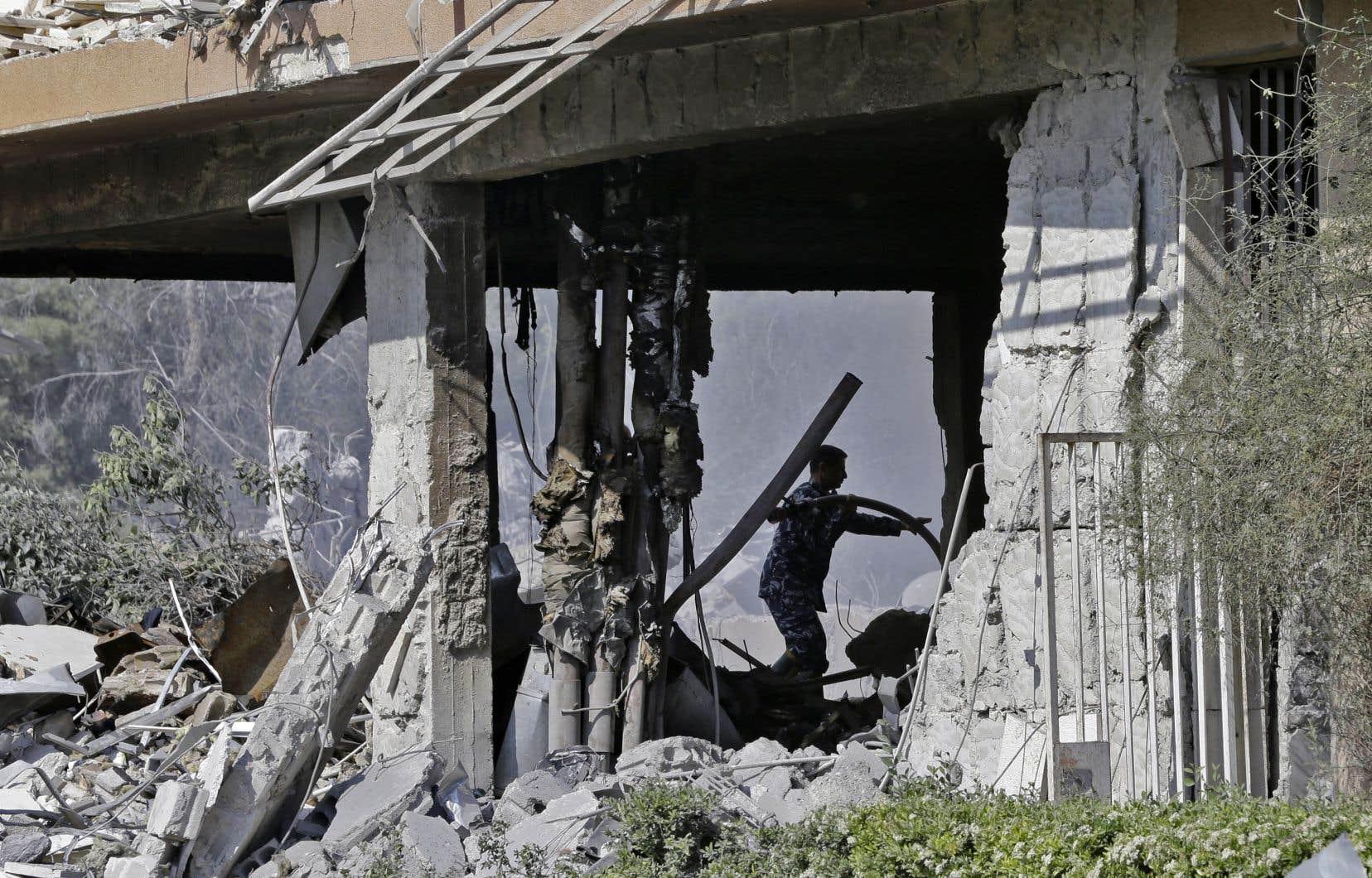 Des soldats syriens inspectent les décombres d'un complexe du Centre d'études et de recherches scientifiques qui a été visé par les frappes occidentales, au nord de Damas, samedi.