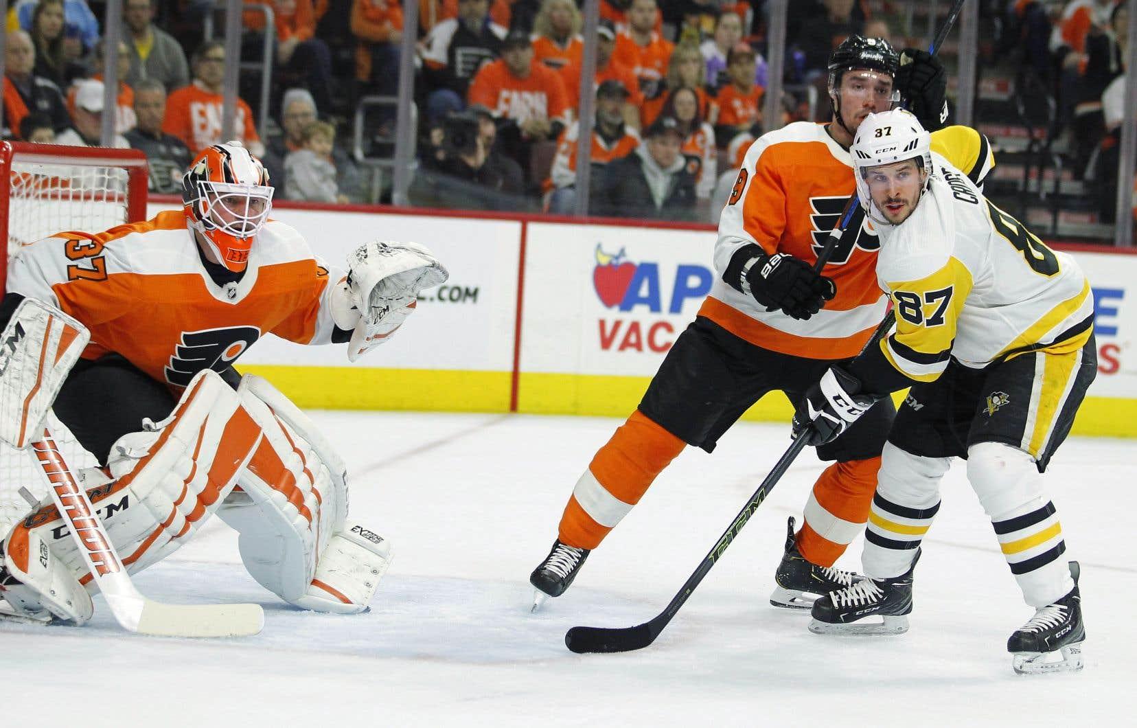 Sidney Crosby des Penguins (à droite) attend devant le filet aux côtés de Brian Elliott (à gauche) et Ivan Povorov des Flyers.