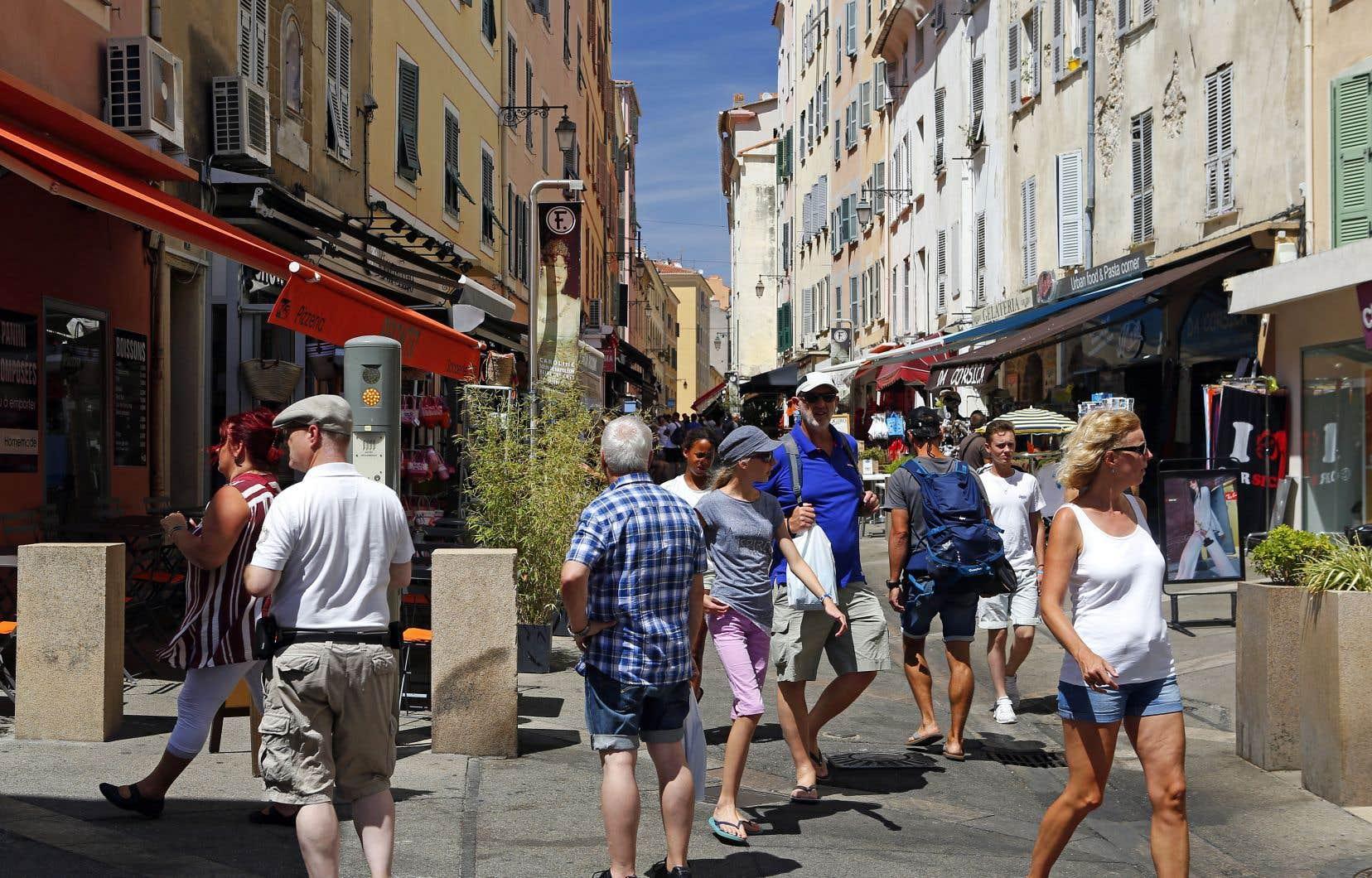 Des touristes marchant dans les rues d'Ajaccio le 27juillet 2017. Deux bateaux de croisière contenant au total quelque 5800 personnes avaient accosté au port de la ville dans la journée.
