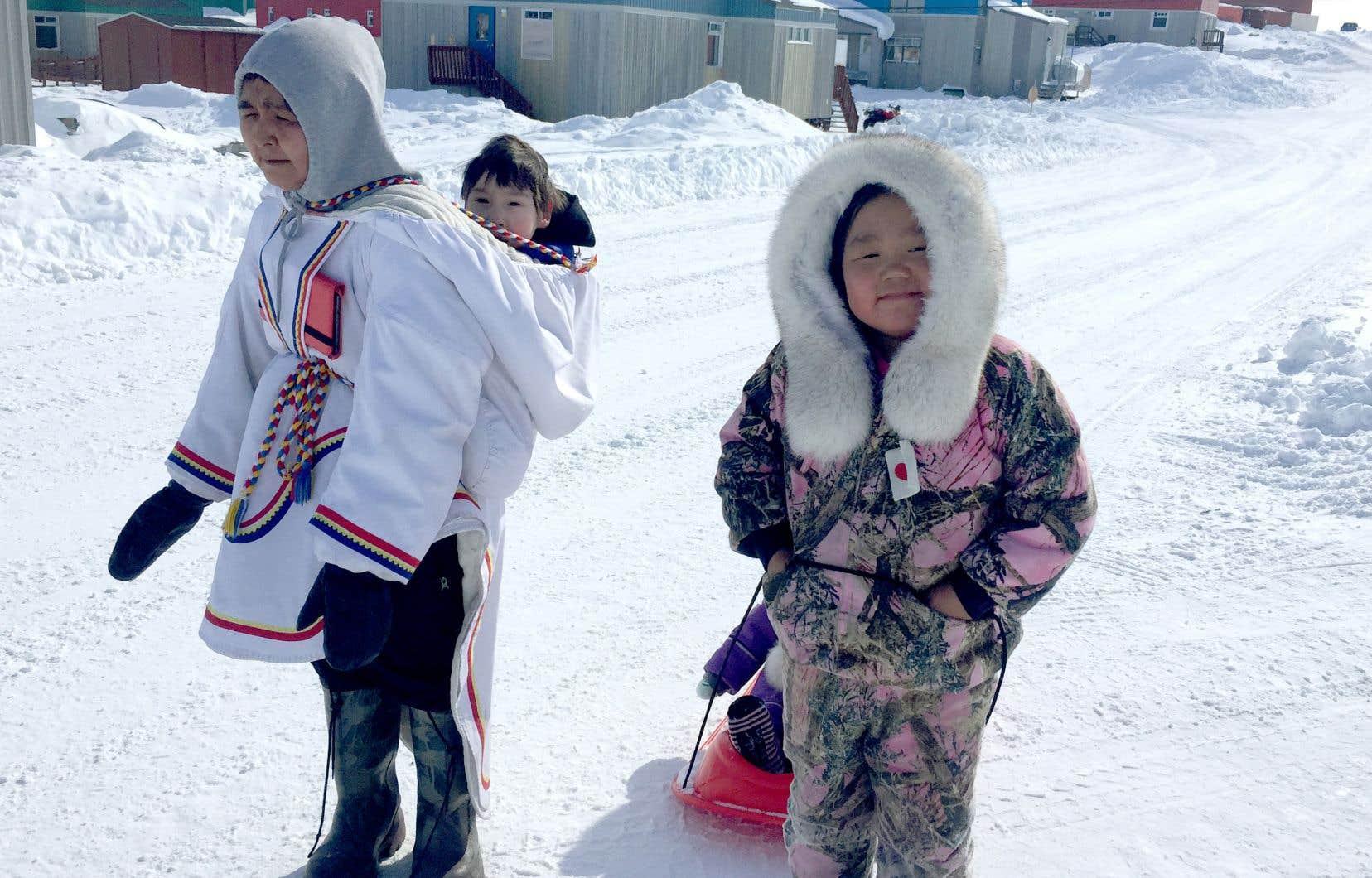 Des hommes d'Inukjuak apprennent aux plus jeunes comment pêcher, chasser et construire un igloo pour se protéger du froid.